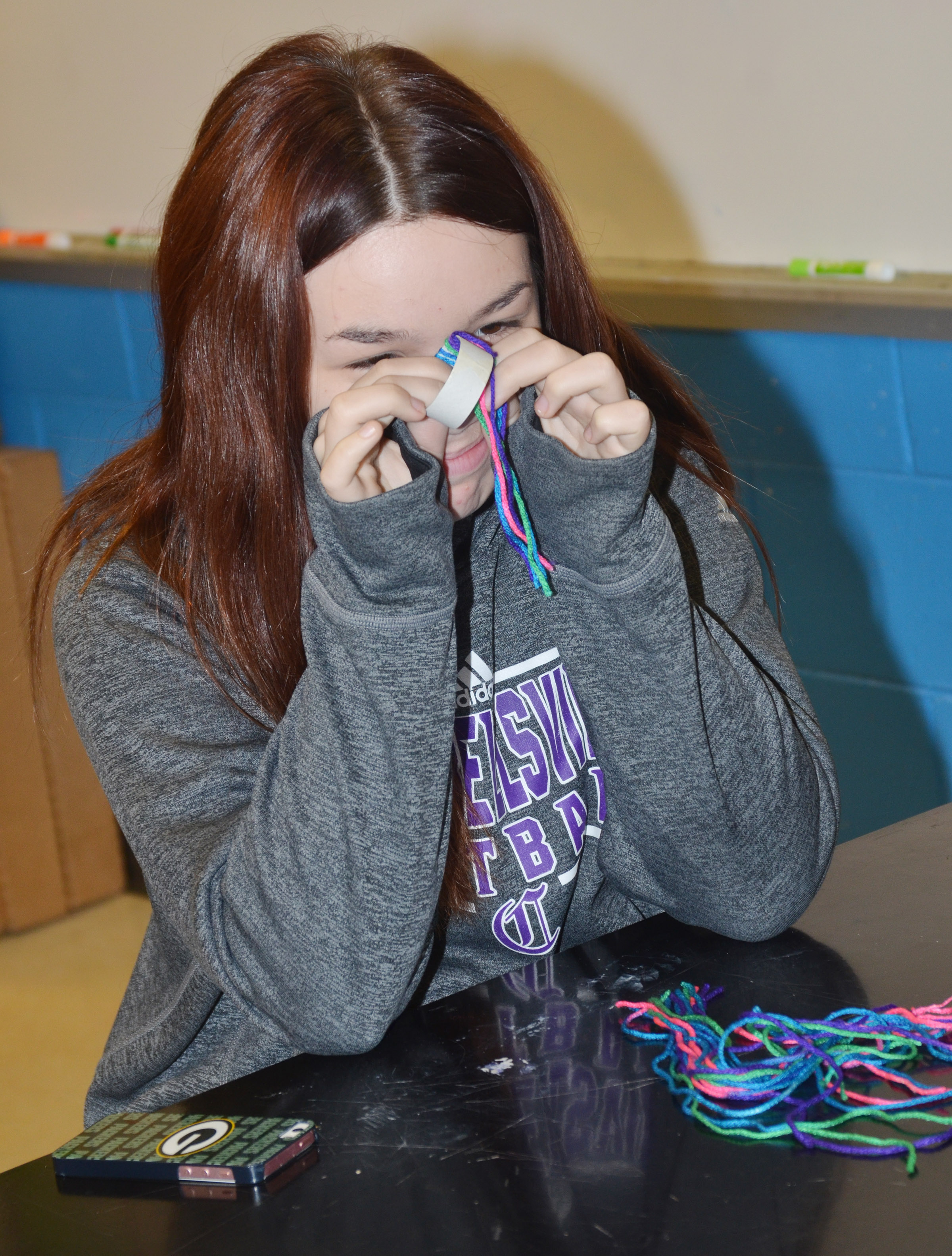 CMS eighth-grader Olivia Fields makes a toboggan out of yarn.