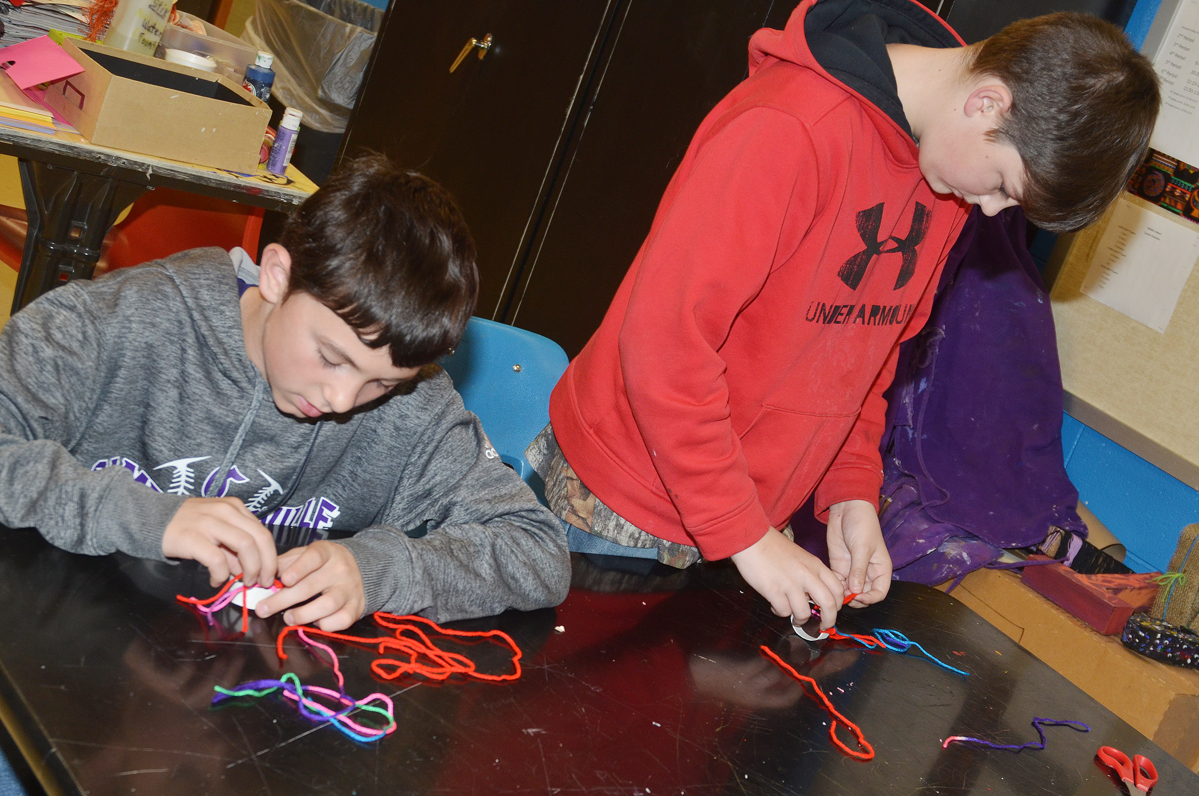 CMS eighth-graders Dakota Harris, at left, and Cohen Moon use yarn to make miniature toboggans.