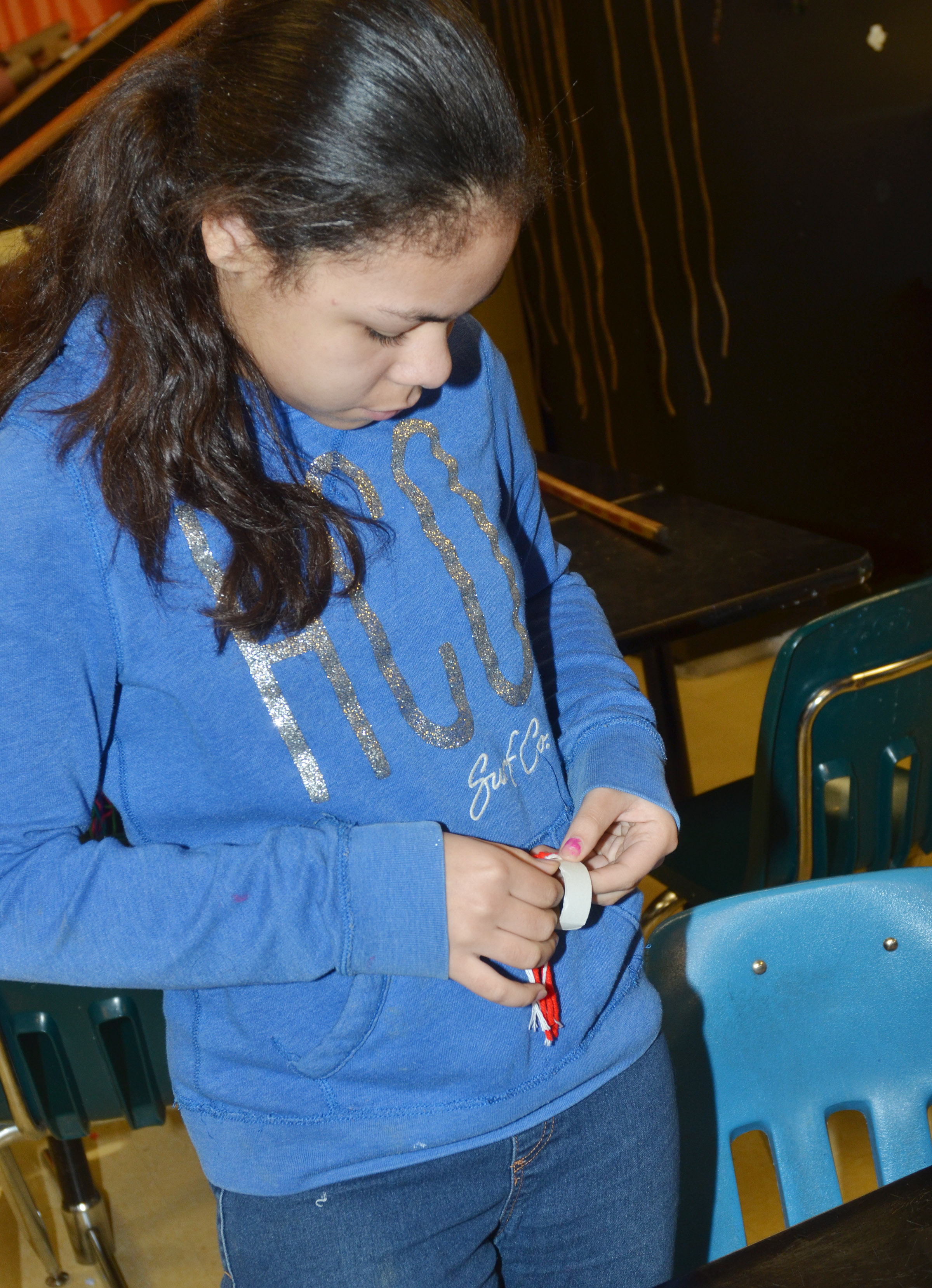 CMS sixth-grader Jayla Penn makes a toboggan out of yarn.