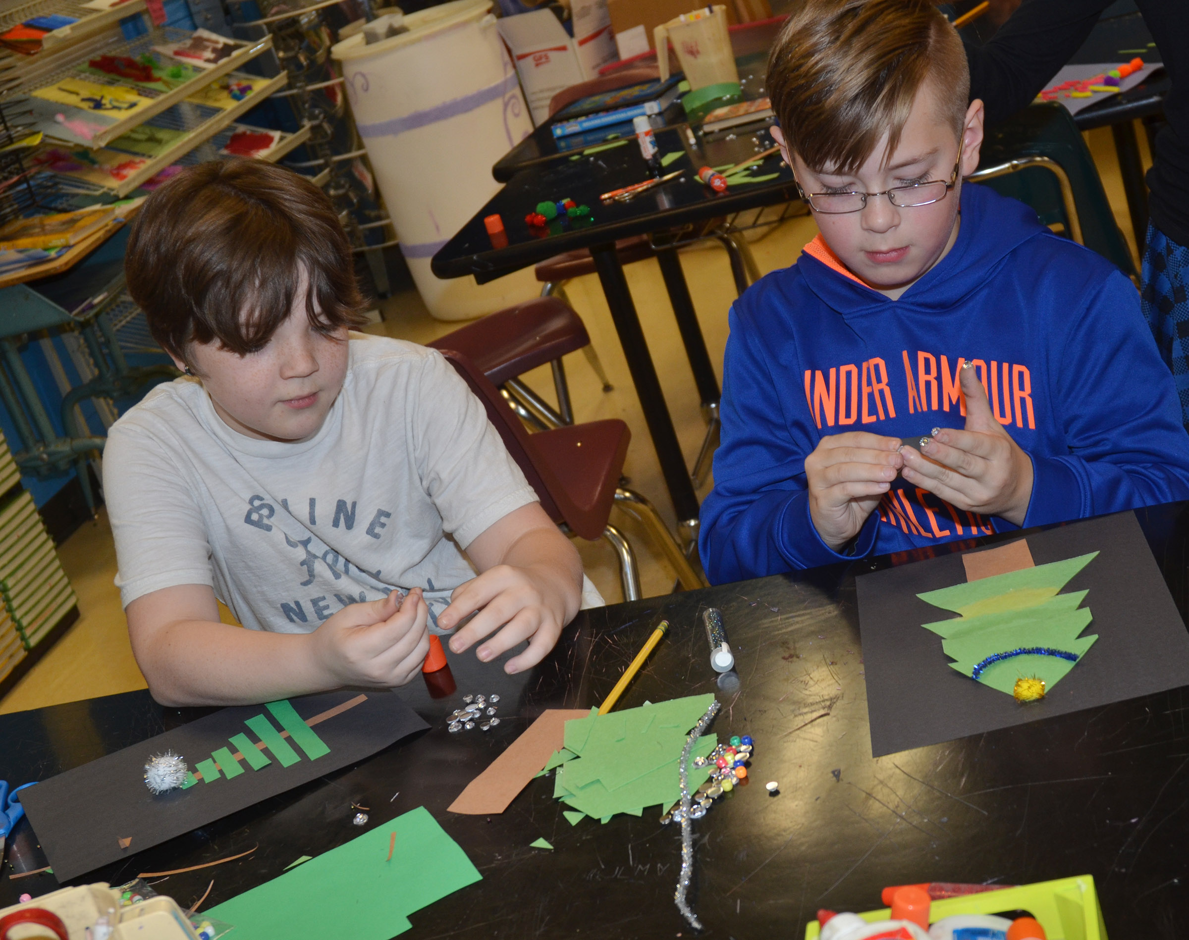 CMS fifth-graders Kayden Birdwell, at left, and Jovi Bowen make their Christmas trees.