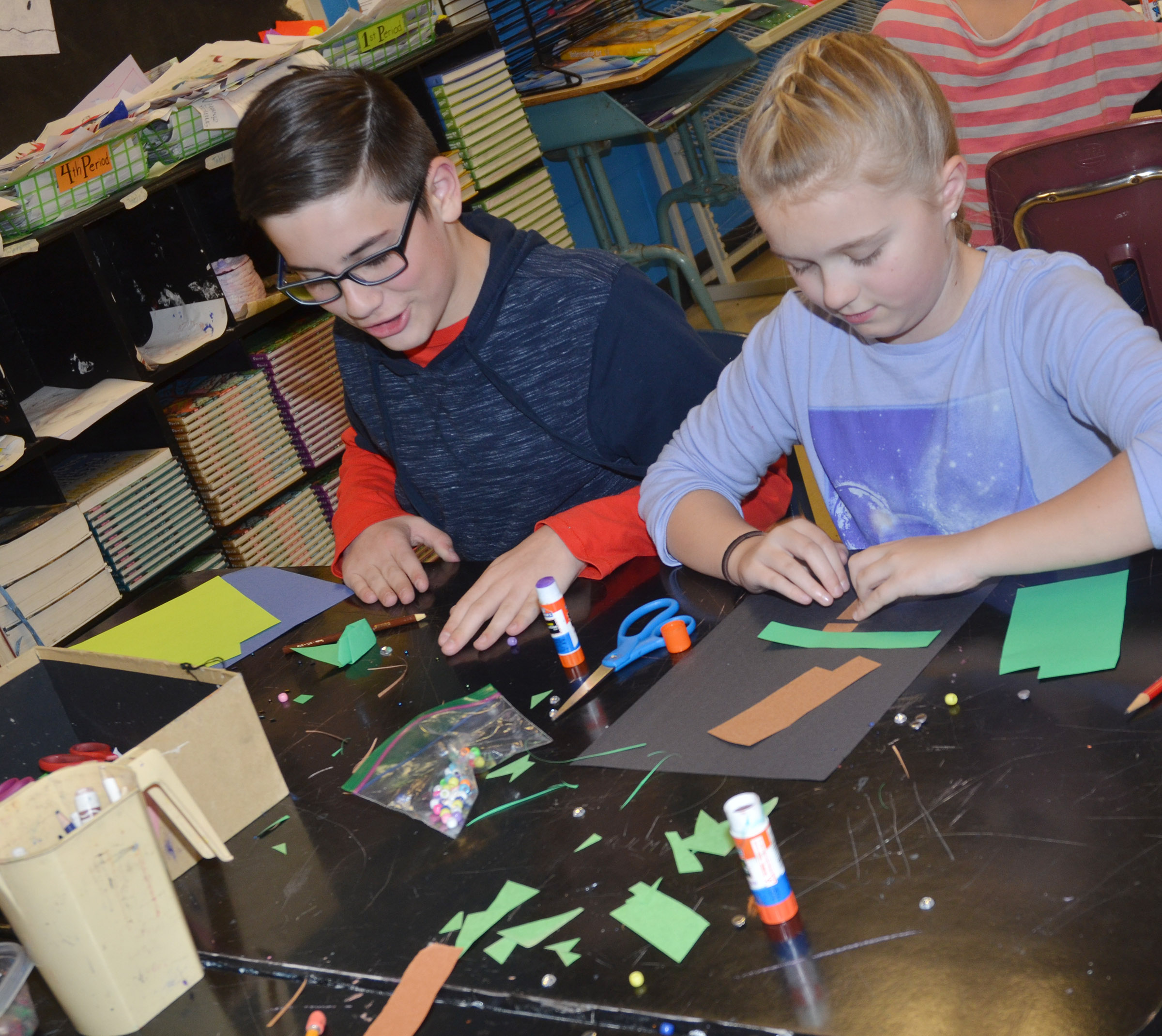 CMS fifth-graders Isaac Garrison, at left, and Lillee Byrne make their Christmas trees.