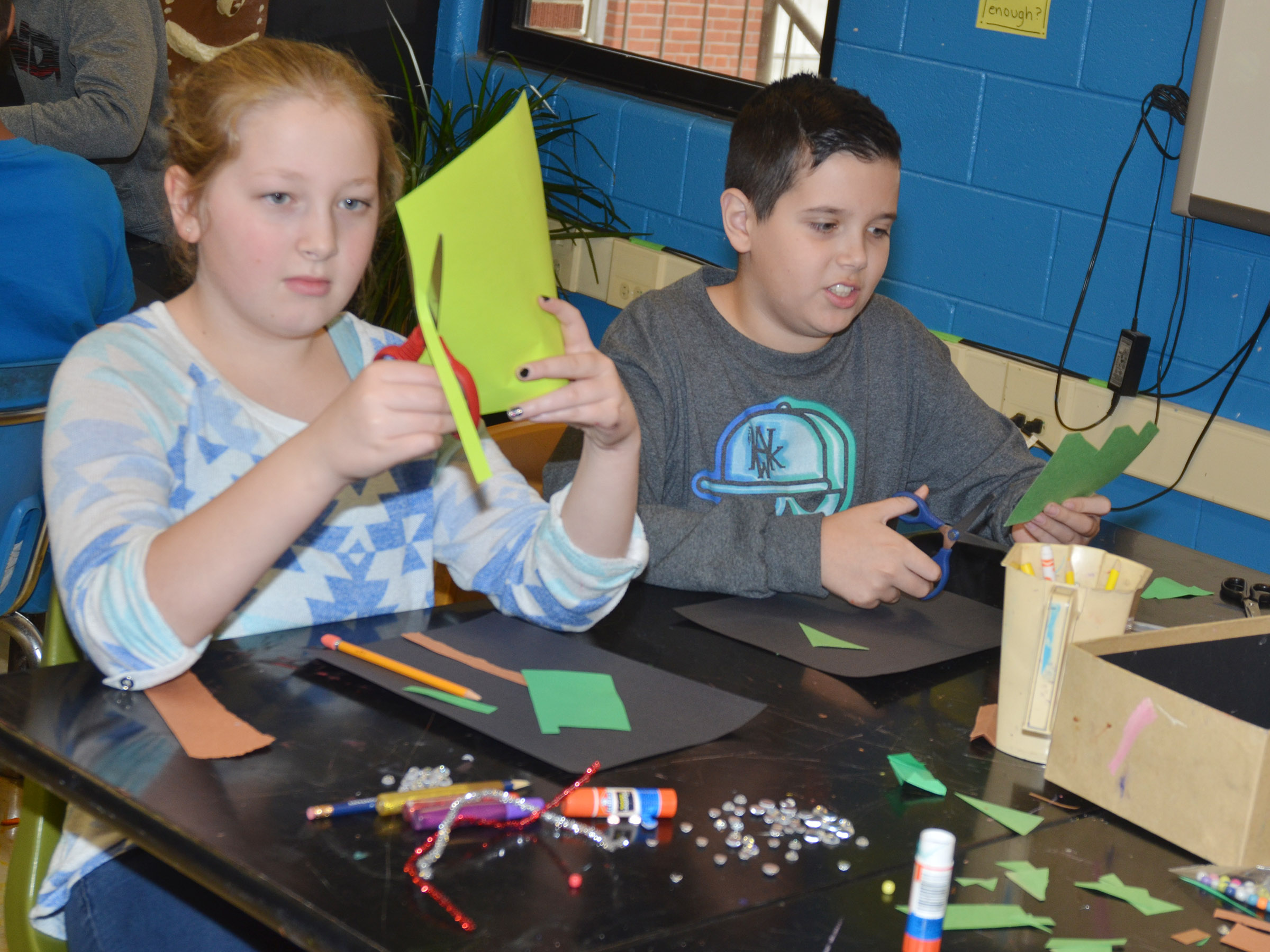 CMS fifth-graders Ava Hughes, at left, and Chase Lawless make their Christmas trees.