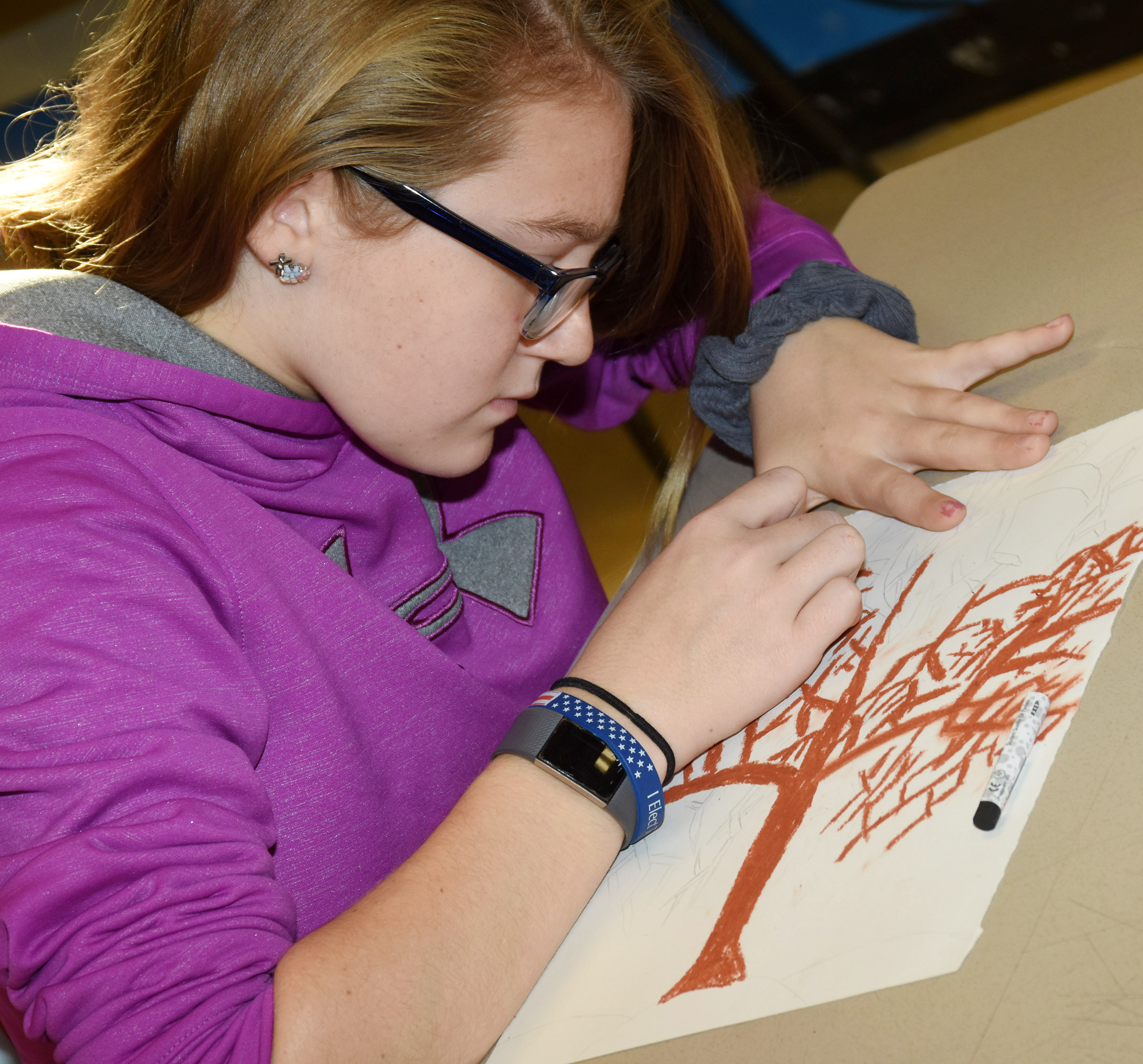 CMS sixth-grader Lilyan Murphy adds color to her tree.