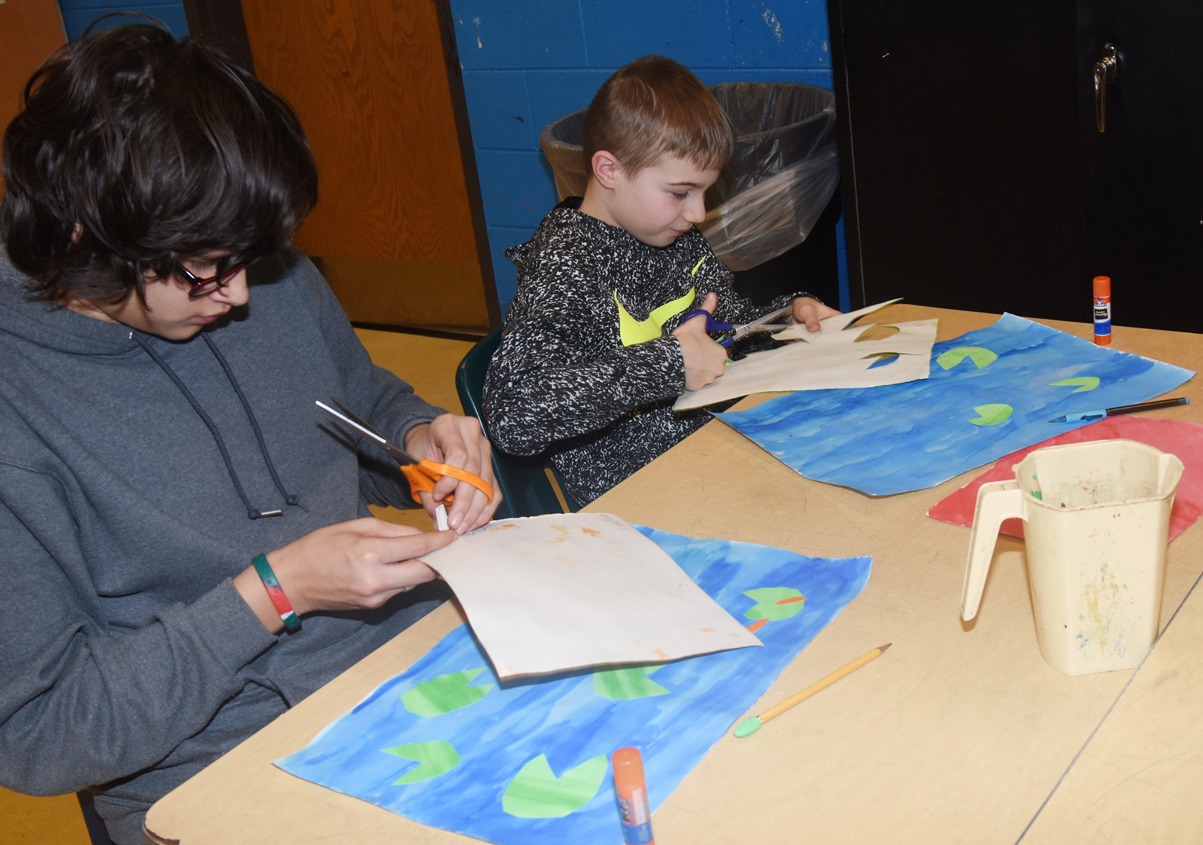 CMS eighth-grader Nate Arachi, at left, and Ethan Cox cut out their lily pads to glue on their paintings.
