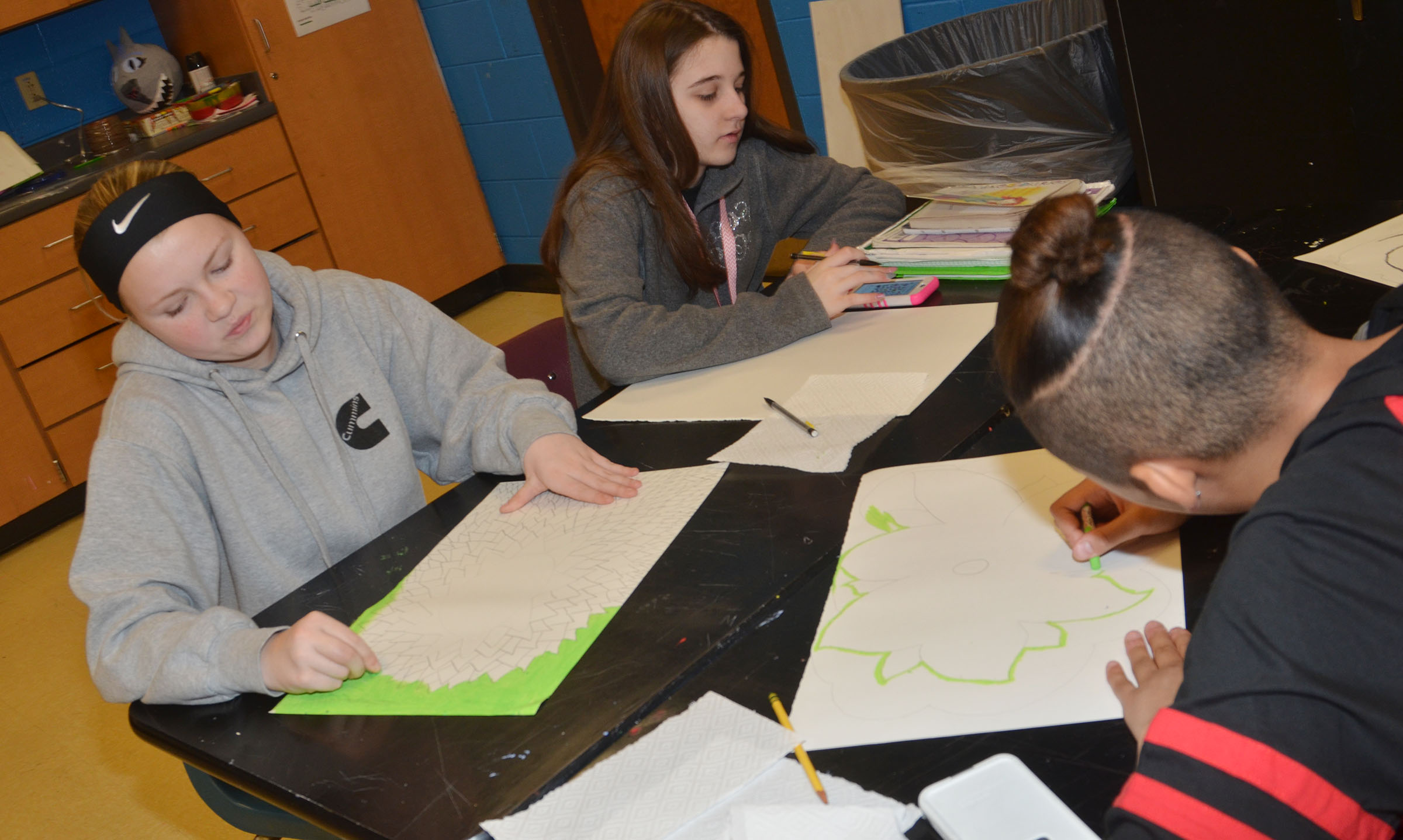 From, CMS eighth-grader Alanna Atwood, Chloe Cox and Taylor Whaley color their flower drawings.