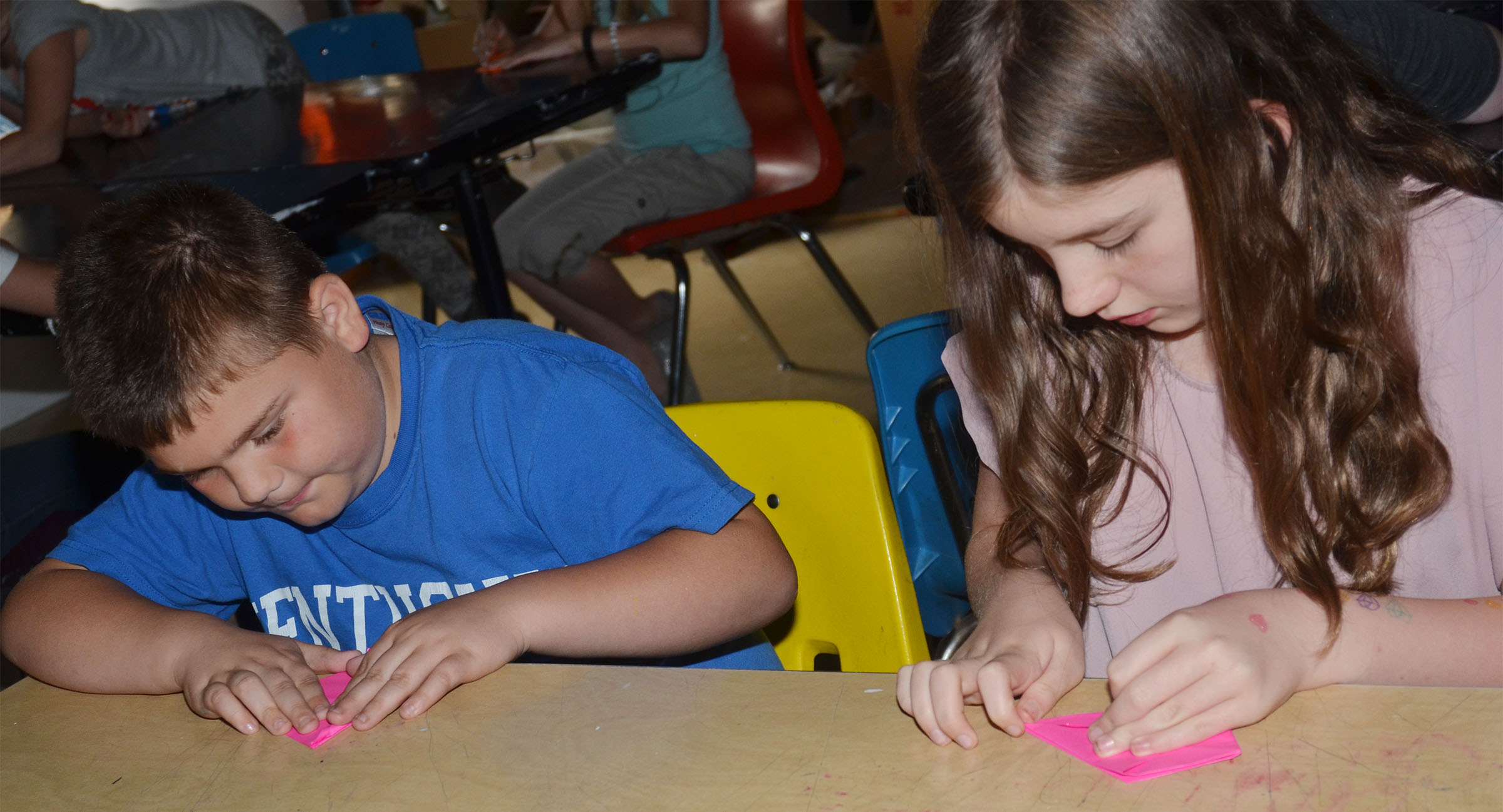 CMS fourth-graders Logan England, at left, and Mikaela Scharbrough make their cranes.