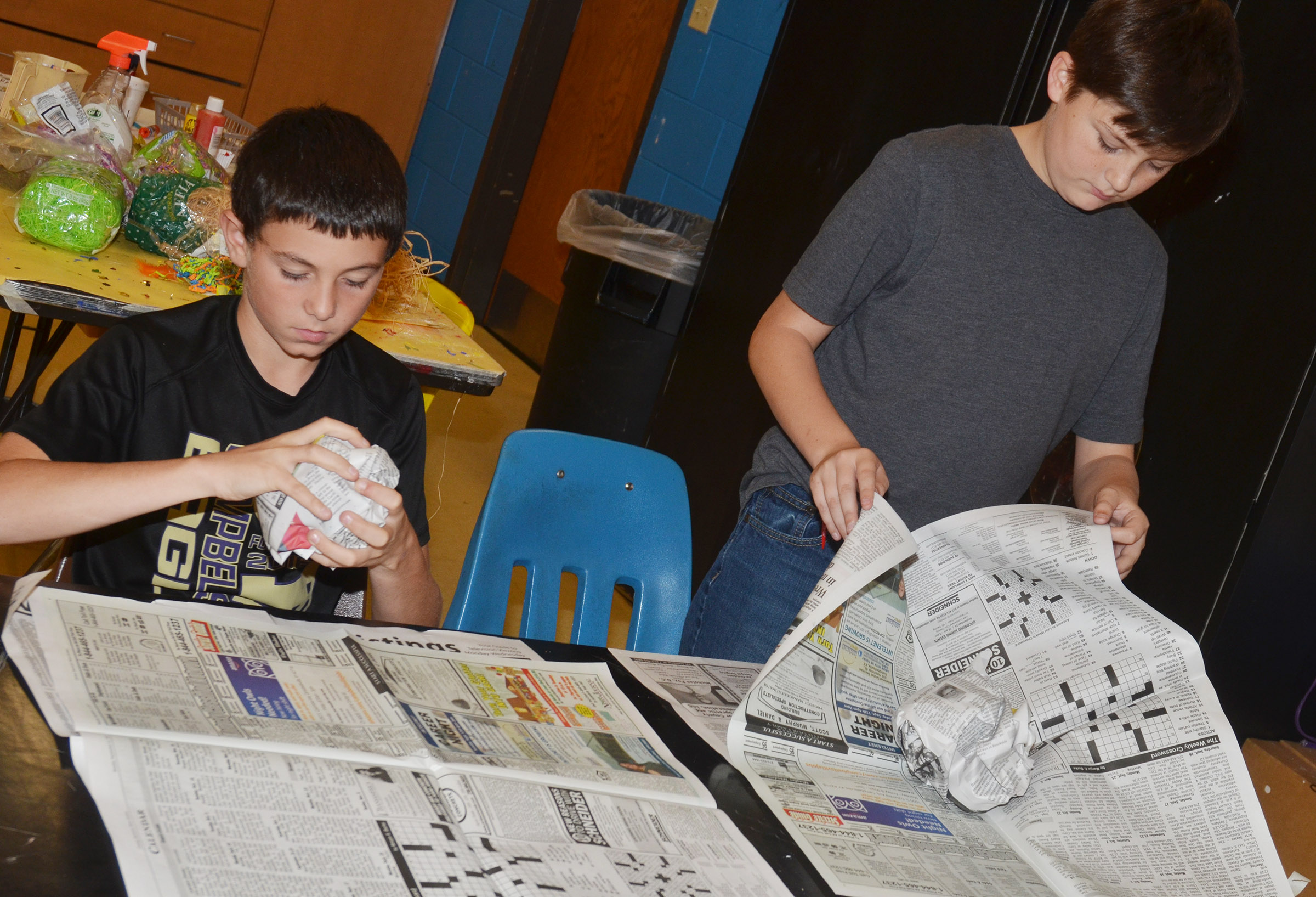 CMS eighth-graders Dakota Harris, at left, and Cohen Moon create their pumpkins out of newspaper.