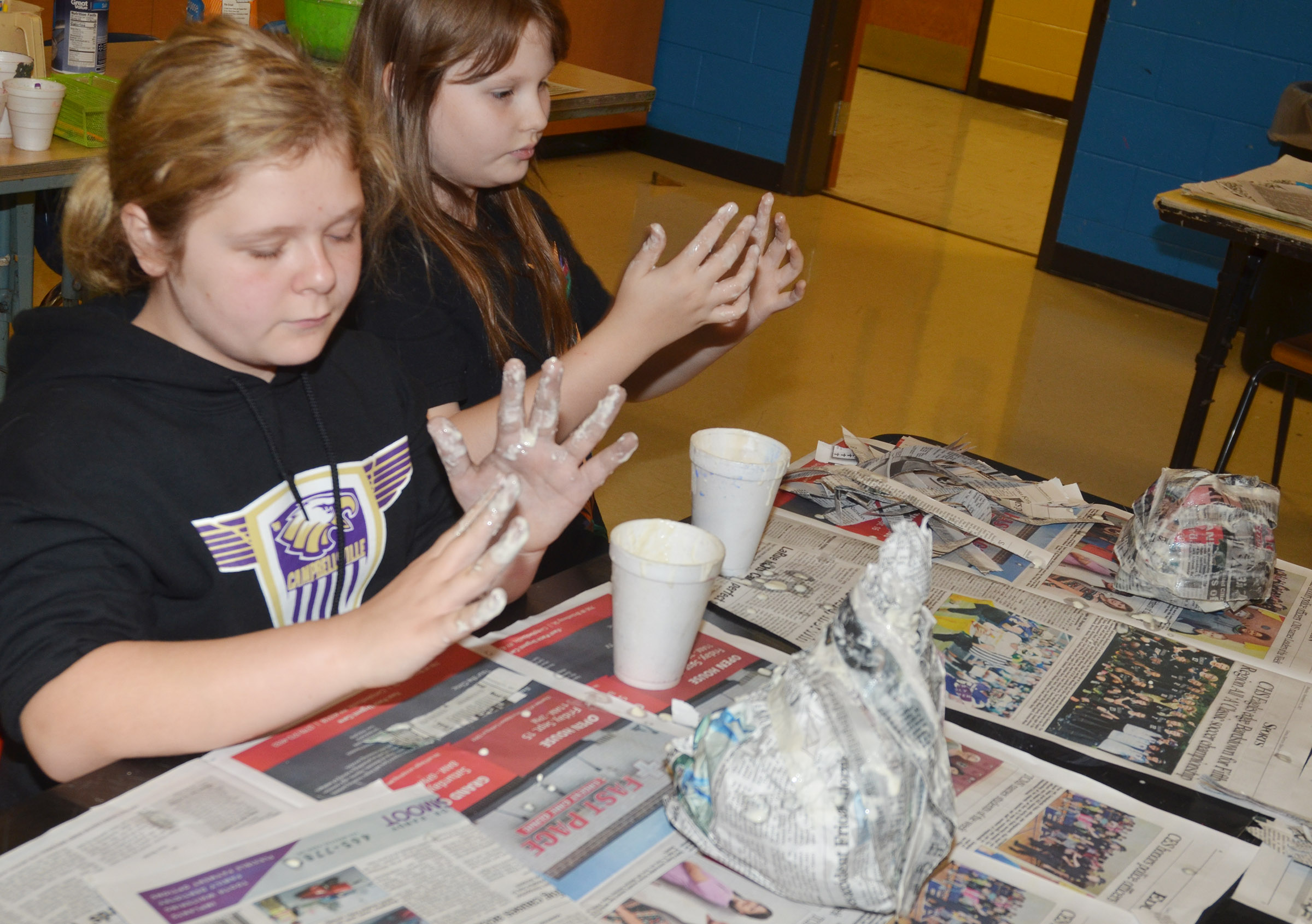 CMS sixth-graders Alexis Sharp, at left, and Savannah Riley add paper mache to their pumpkins.