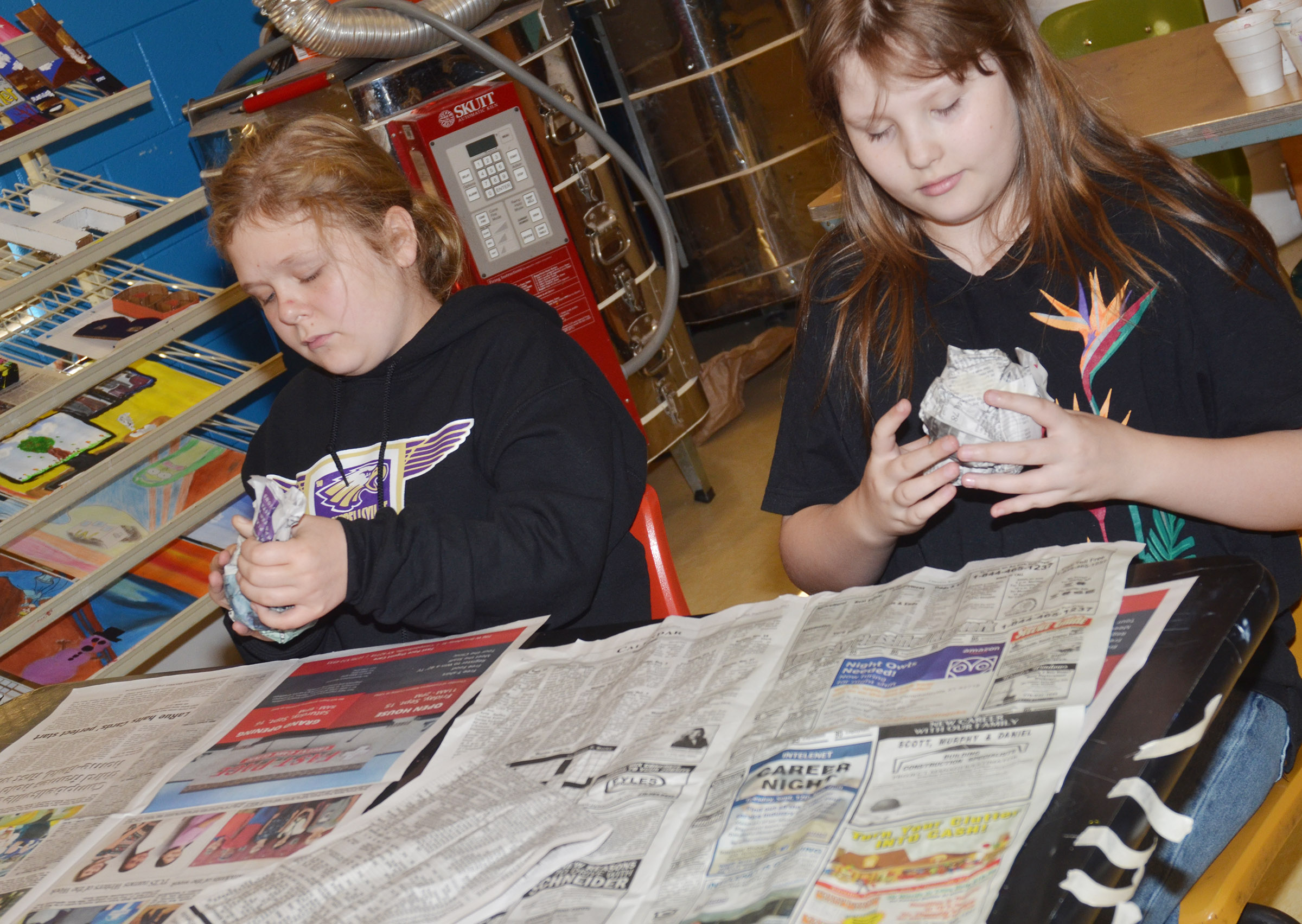 CMS sixth-graders Alexis Sharp, at left, and Savannah Riley make their pumpkins out of newspaper.