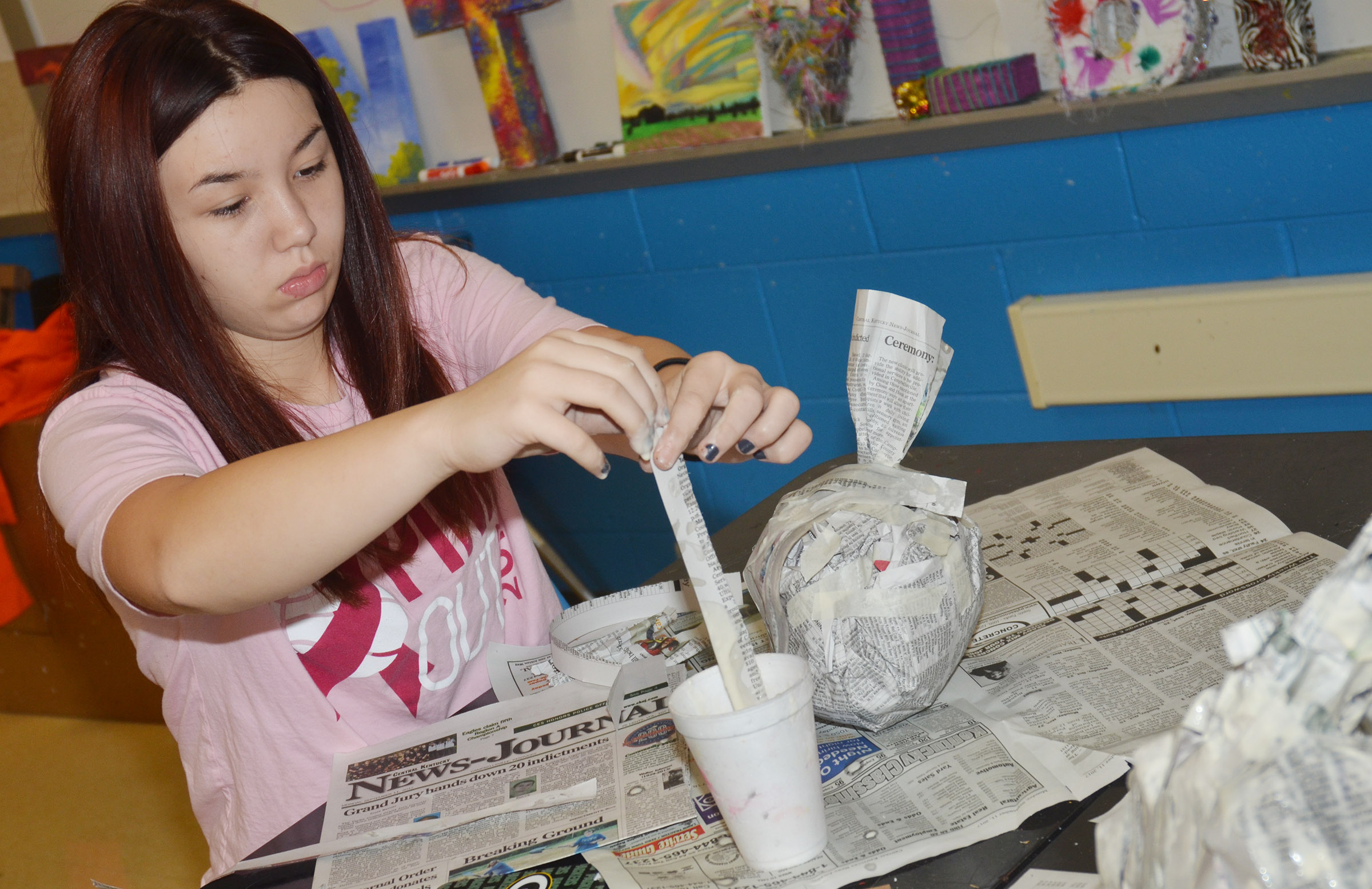 CMS eighth-grader Olivia Fields adds paper mache to her pumpkin.