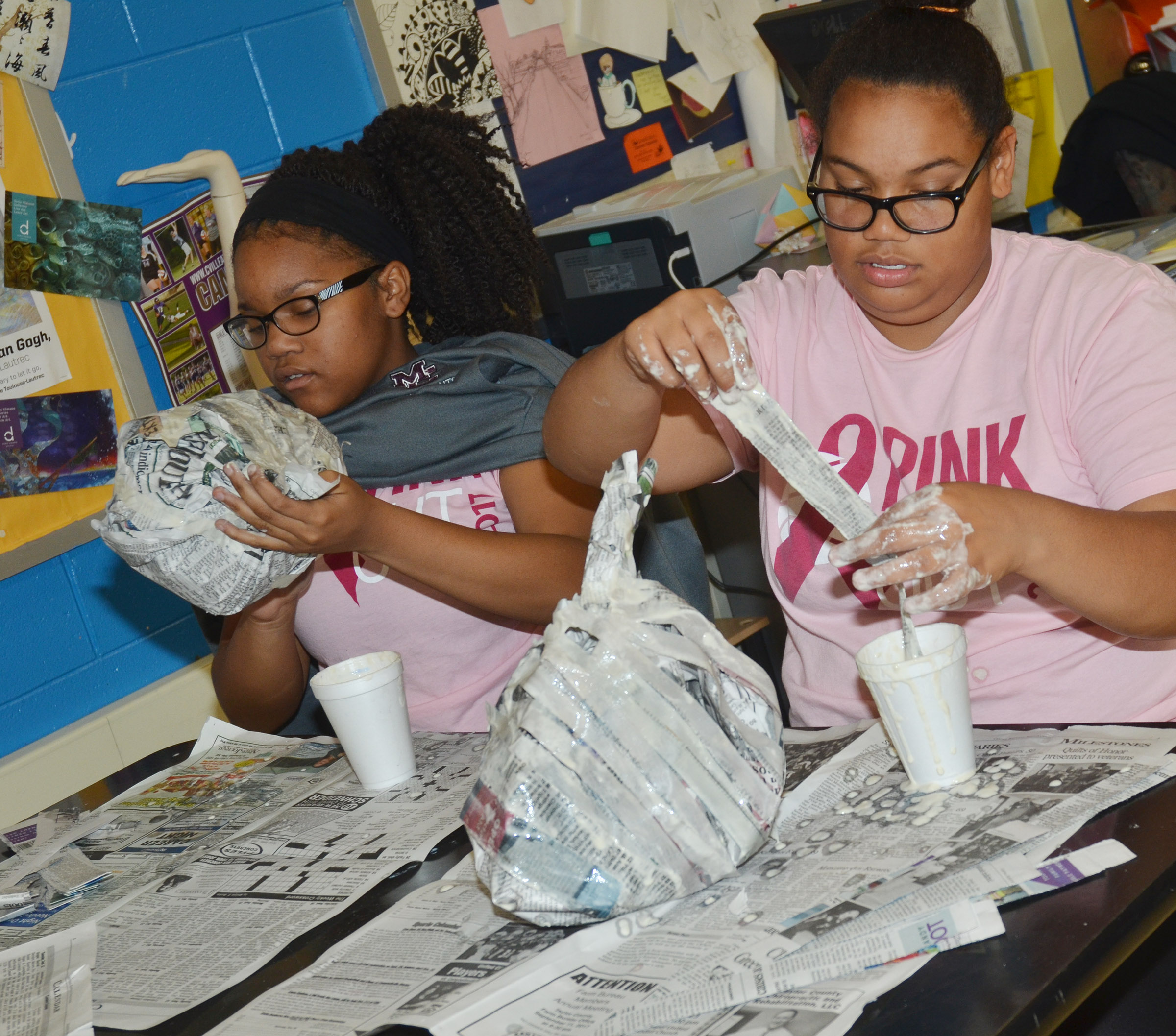 CMS seventh-grader Antaya Epps, at left, and Brae Washington add paper mache to their pumpkins.