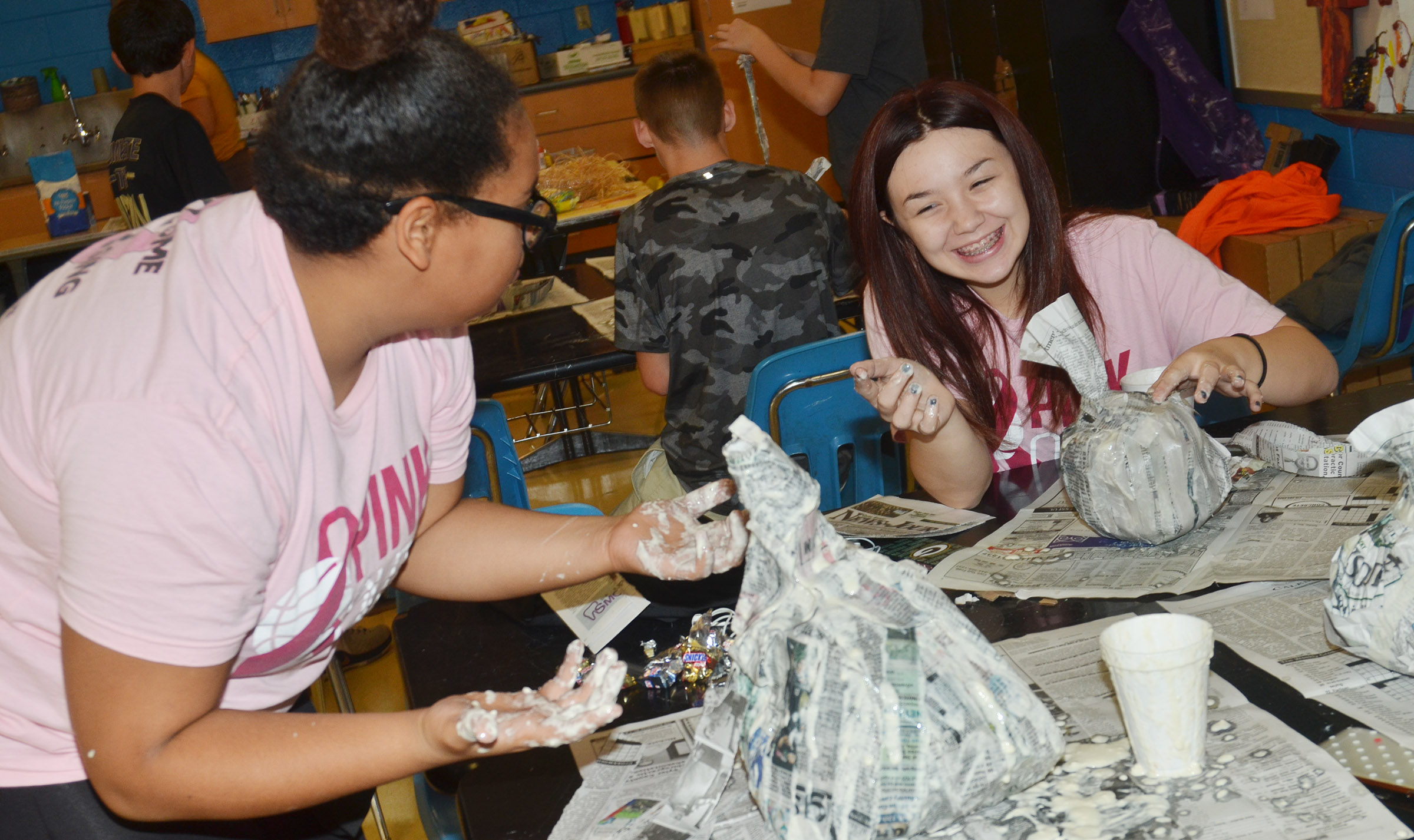 CMS eighth-graders Brae Washington, at left, and Olivia Fields laugh as they add paper mache to their pumpkins.