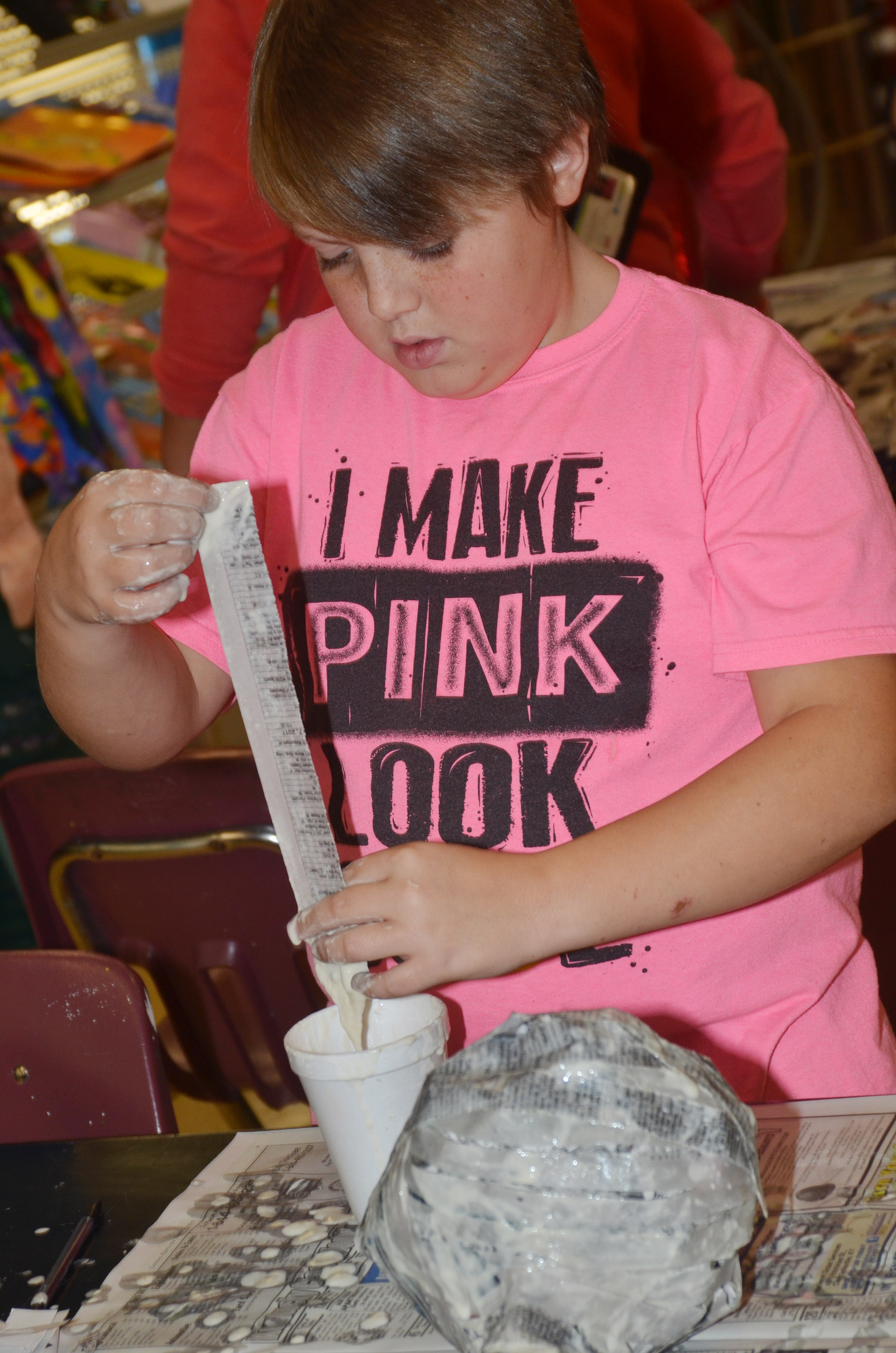 CMS sixth-grader Nathan Ray adds paper mache to his pumpkin.