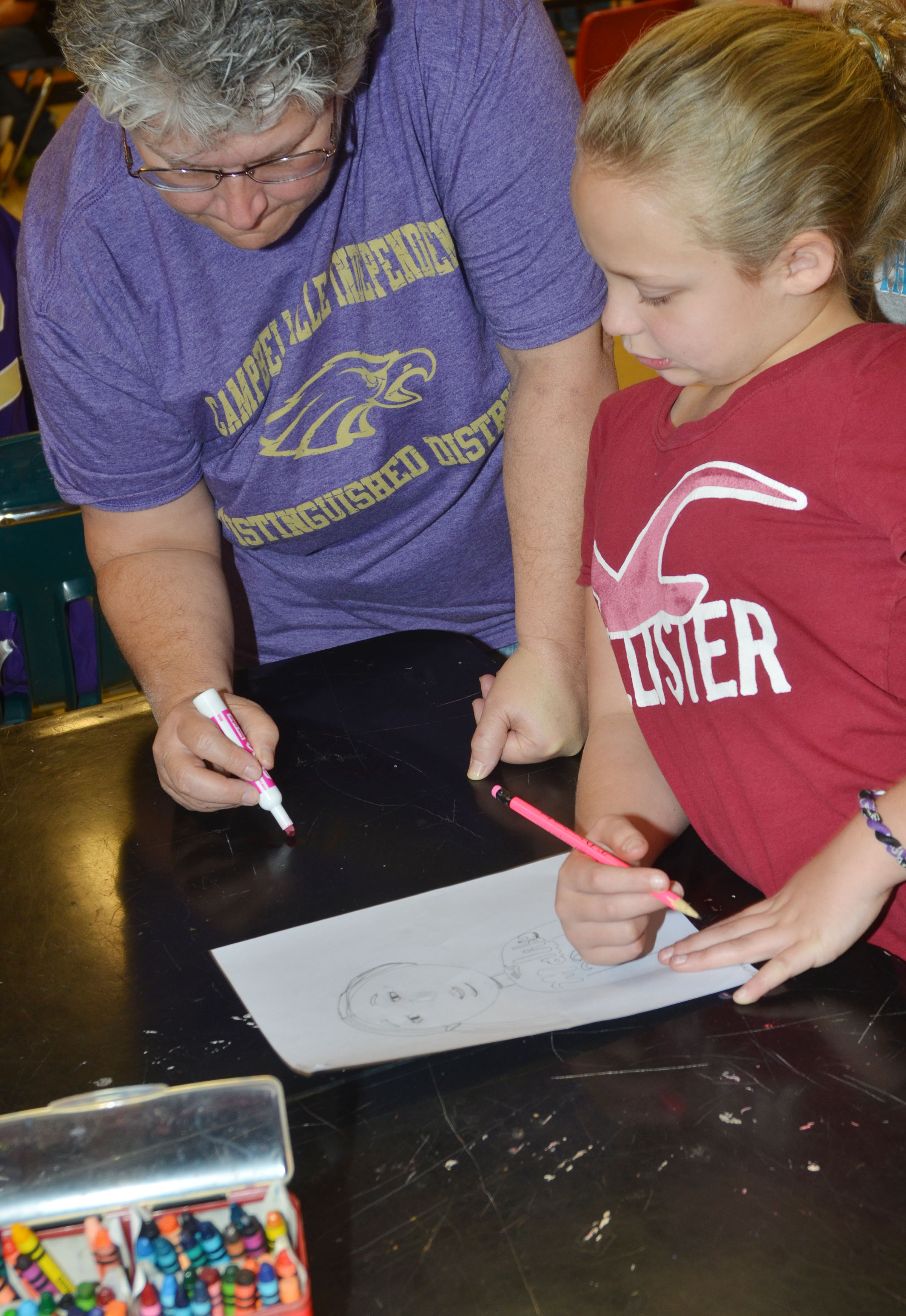 CMS art teacher Jo Ann Harris talks to fourth-grader Deanna Reardon about how to draw facial features.
