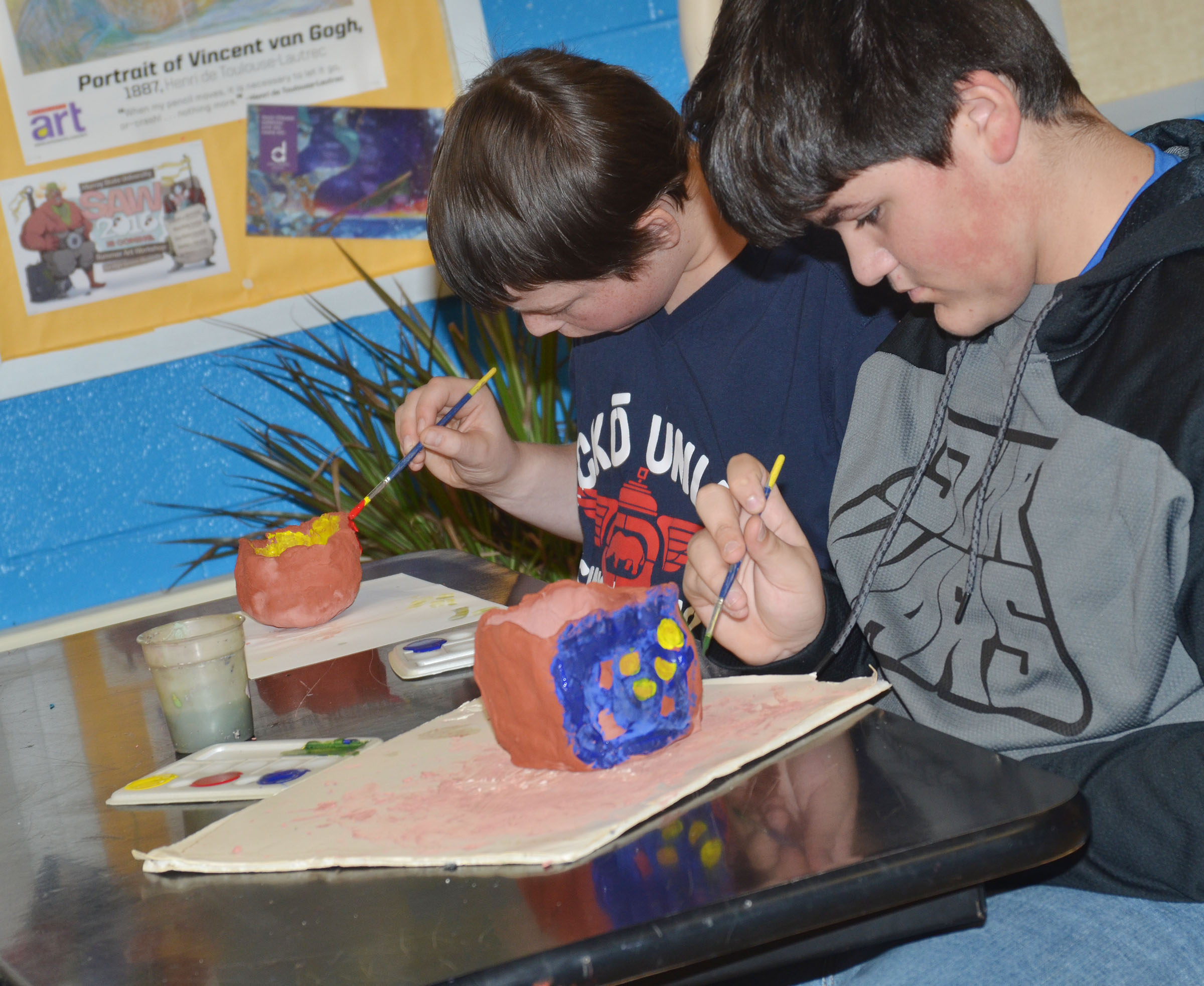 CMS seventh-graders Takyia Cox, at left, and Logan Rakes paint their pots.