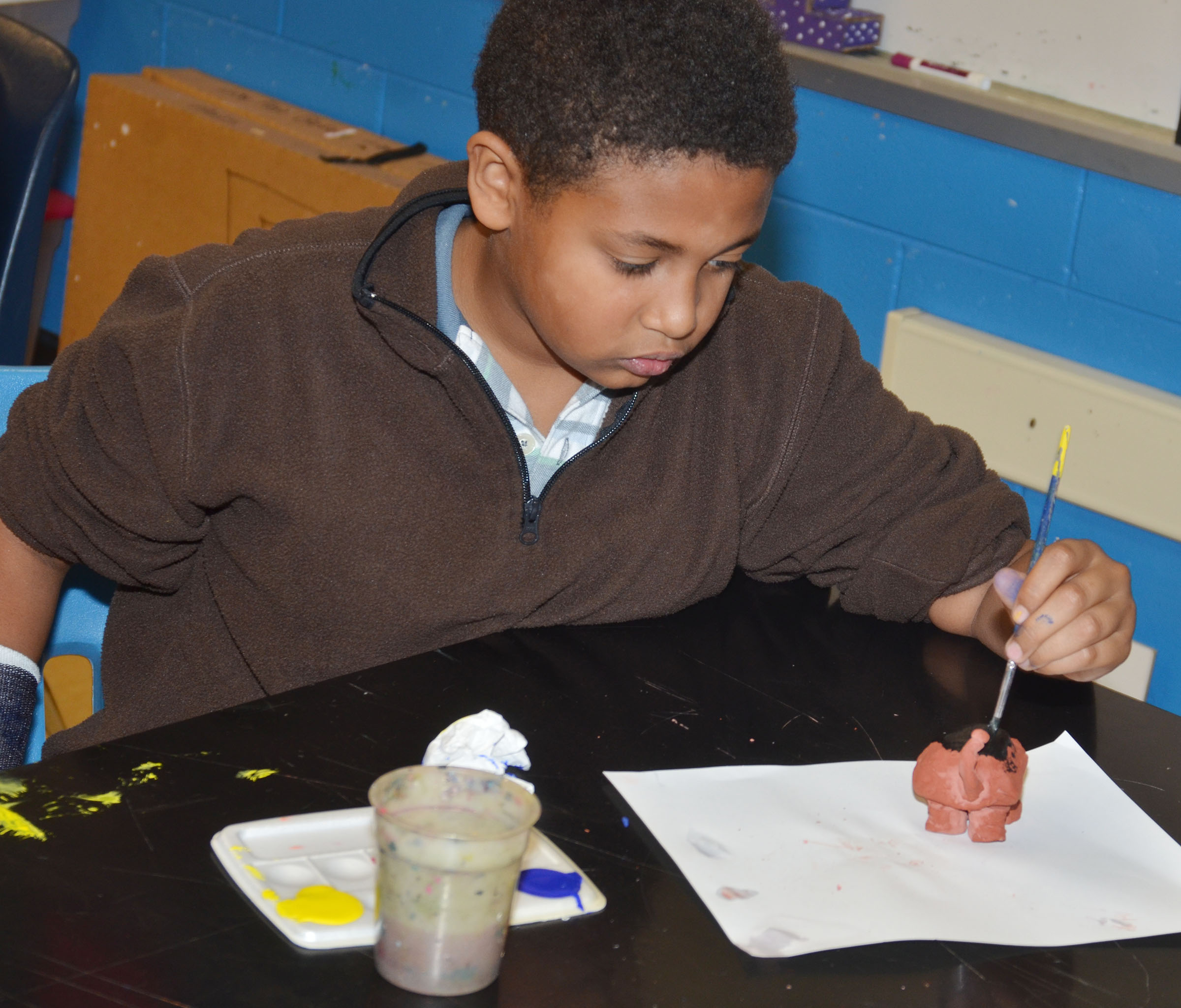 CMS sixth-grader Ronin Smith paints his pot.