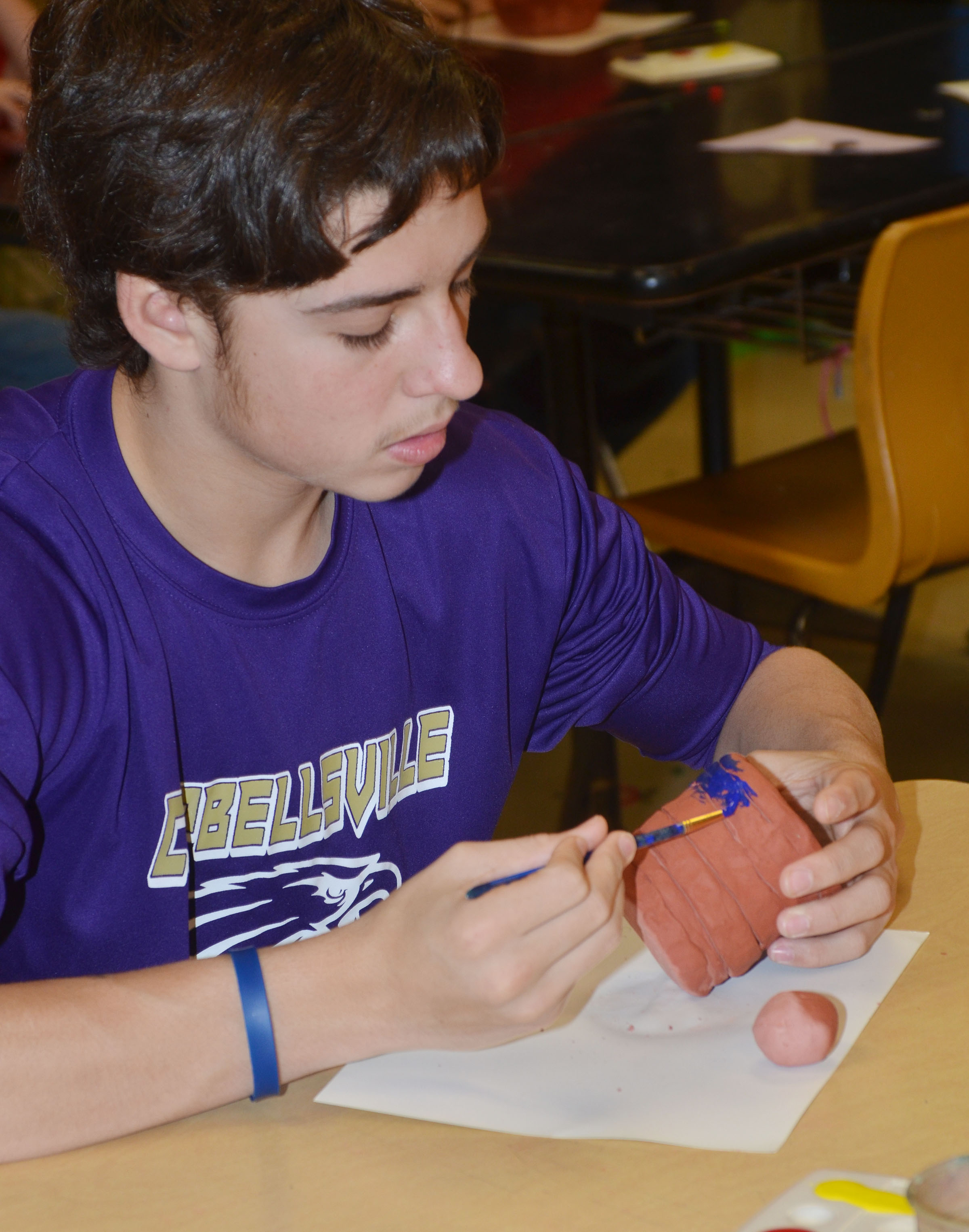 CMS eighth-grader John Orberson paints his pot.