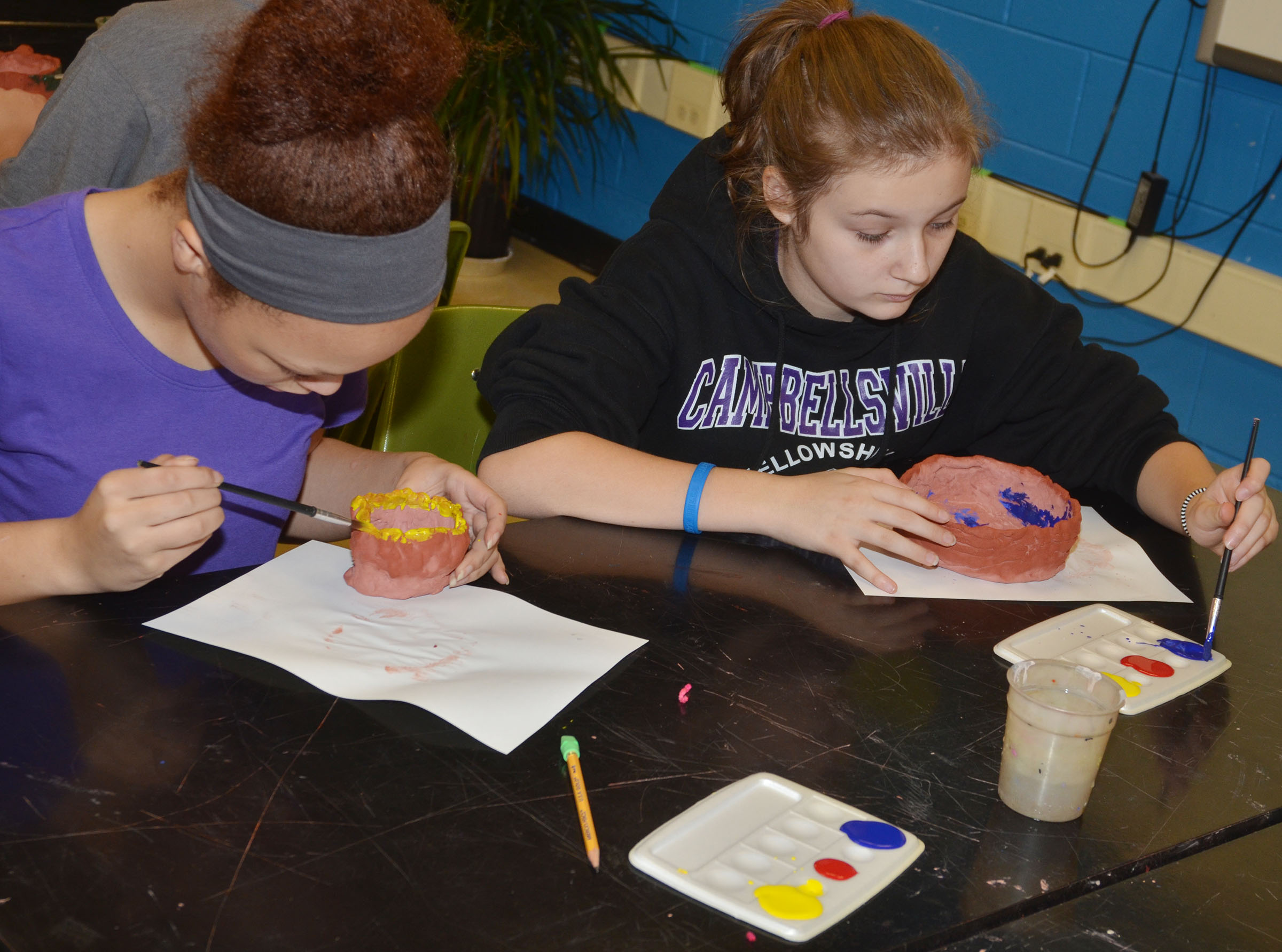 CMS seventh-graders Kitana Taylor, at left, and Serenity Ford paint their pots.