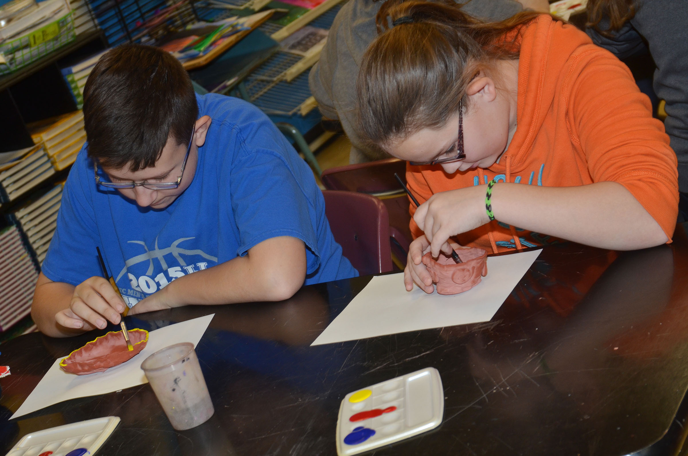 CMS eighth-graders Nathan Sowders, at left, and Xierra Underwood paint their pots.