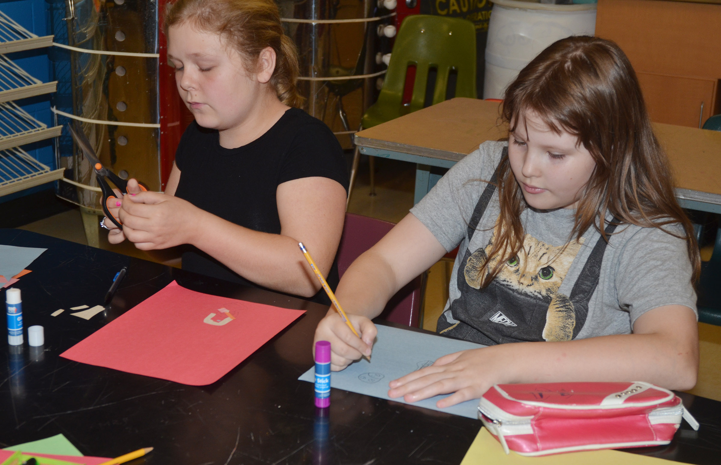 CMS sixth-graders Alexis Sharp, at left, and Savannah Riley create their collages.