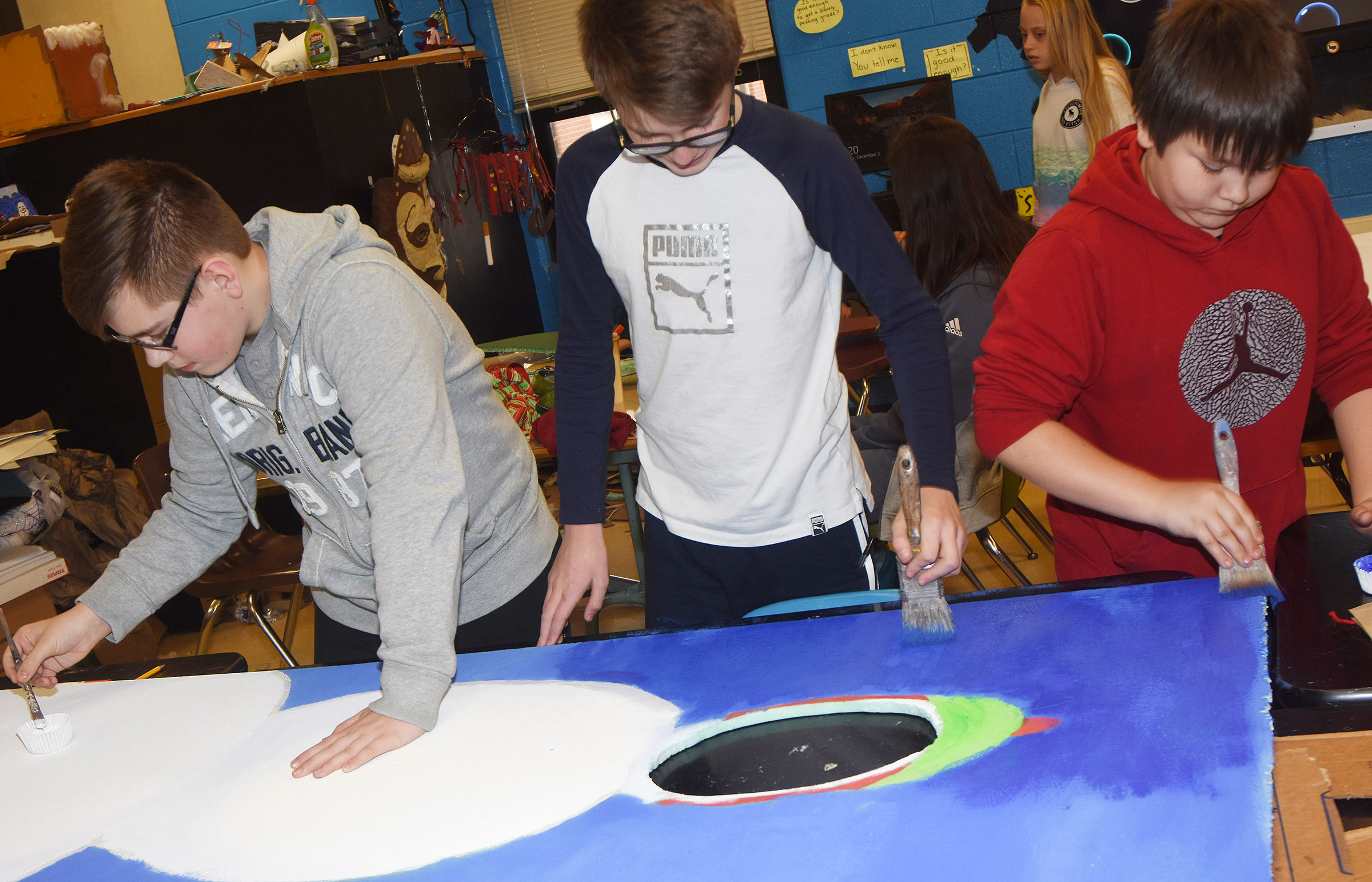 From left, CMS seventh-graders Jovi Bowen, Ethan Murphy and Leo Lamer paint a snowman photo backdrop.