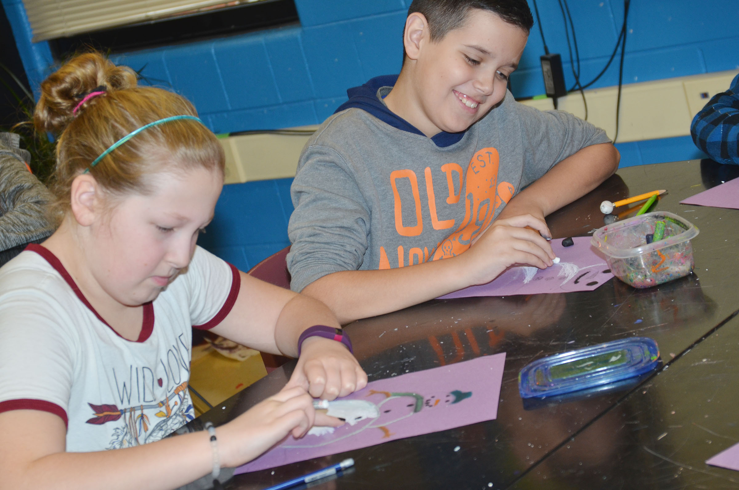 CMS fifth-grader Ava Hughes, at left, and Chase Lawless color their snowmen.