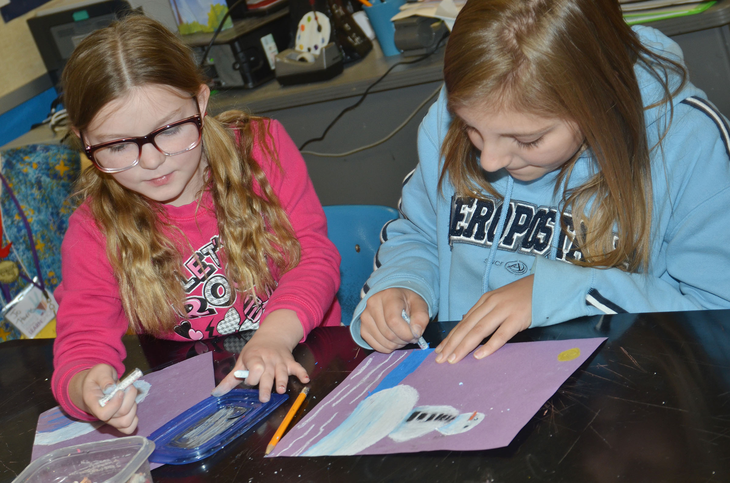 CMS fifth-graders Morgan Spears, at left, and Grace Tungate color their snowman scenes.