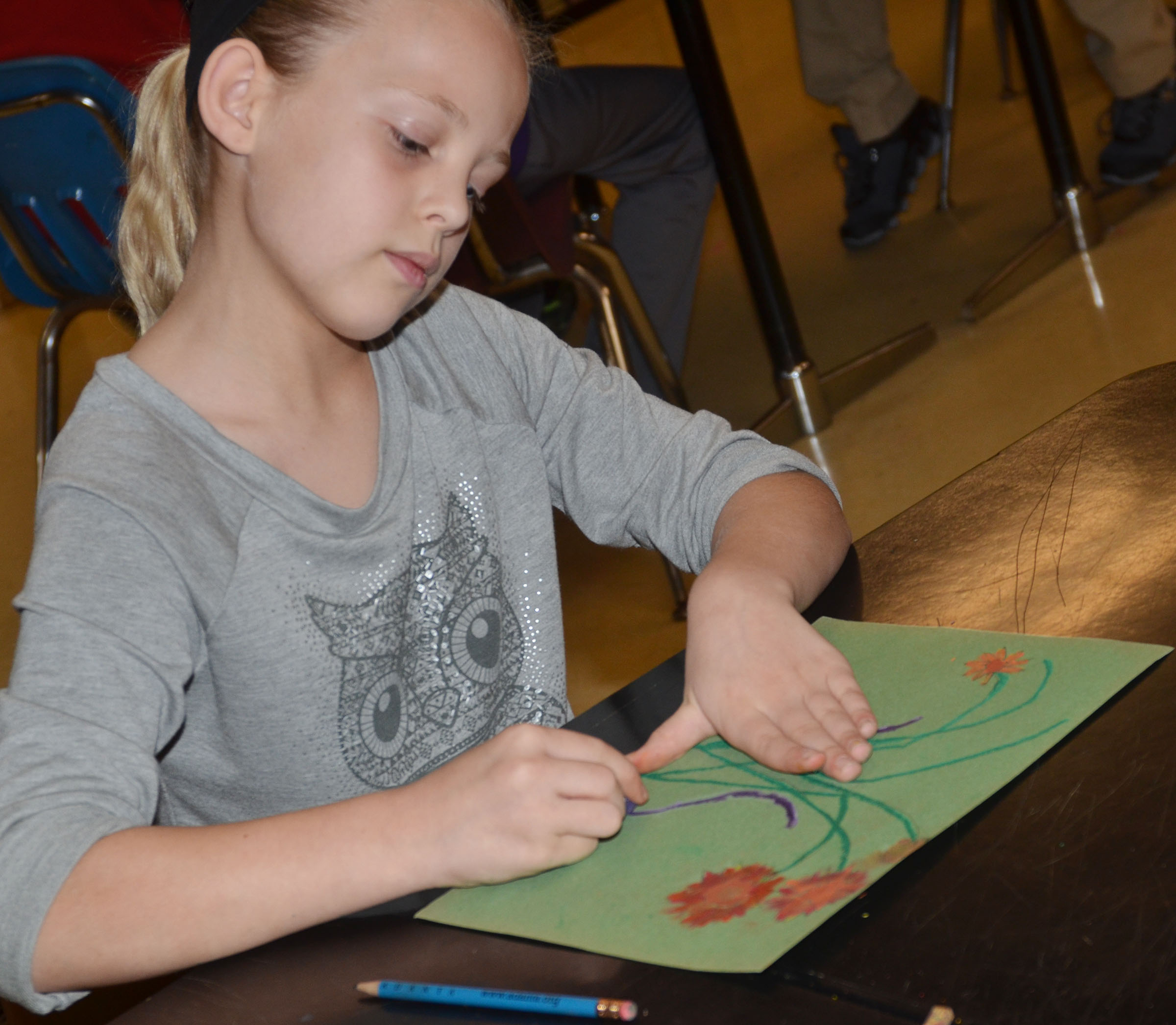 CMS fifth-grader Gabby Bright colors her sunflower drawing with oil pastels.