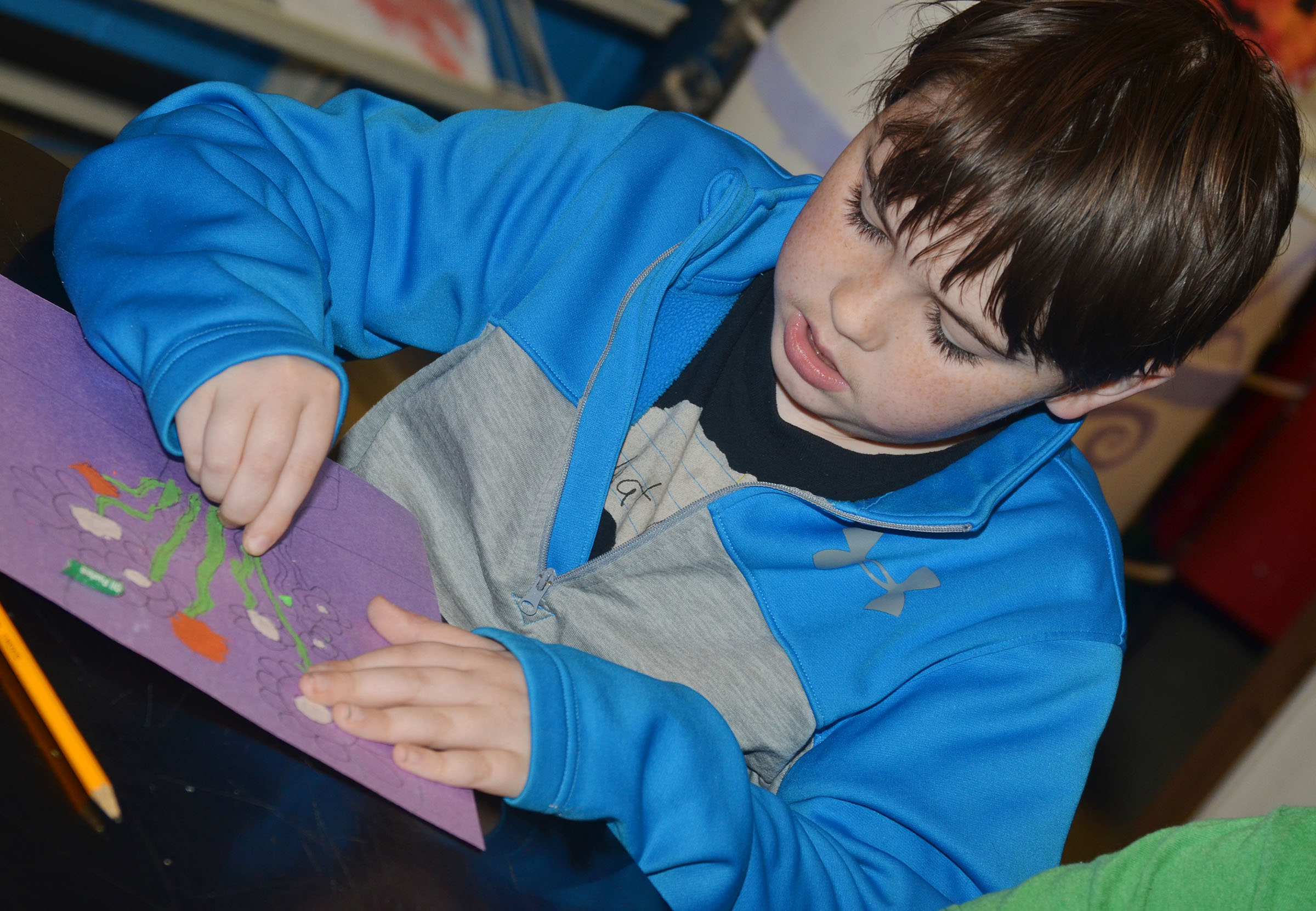 CMS fourth-grader Cody Agee colors his sunflower drawing with oil pastels.