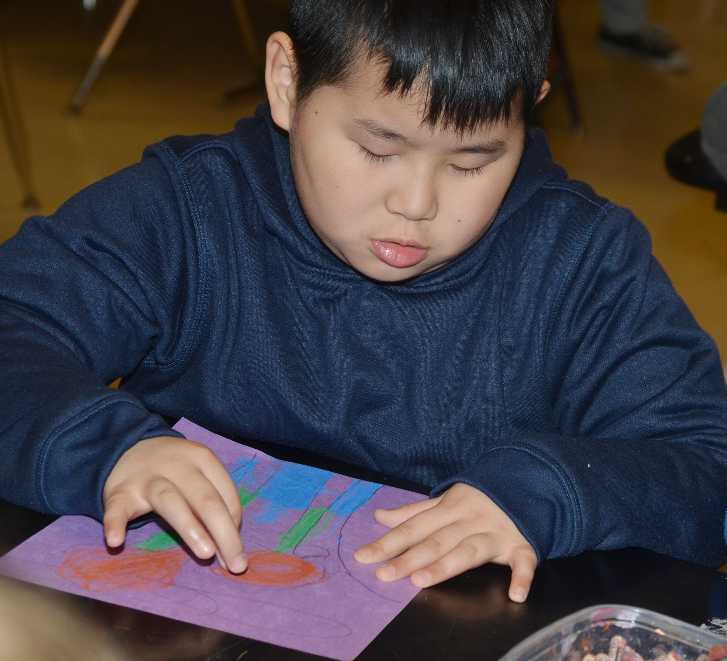 CMS fourth-grader Zhi Chen colors his sunflower drawing with oil pastels.