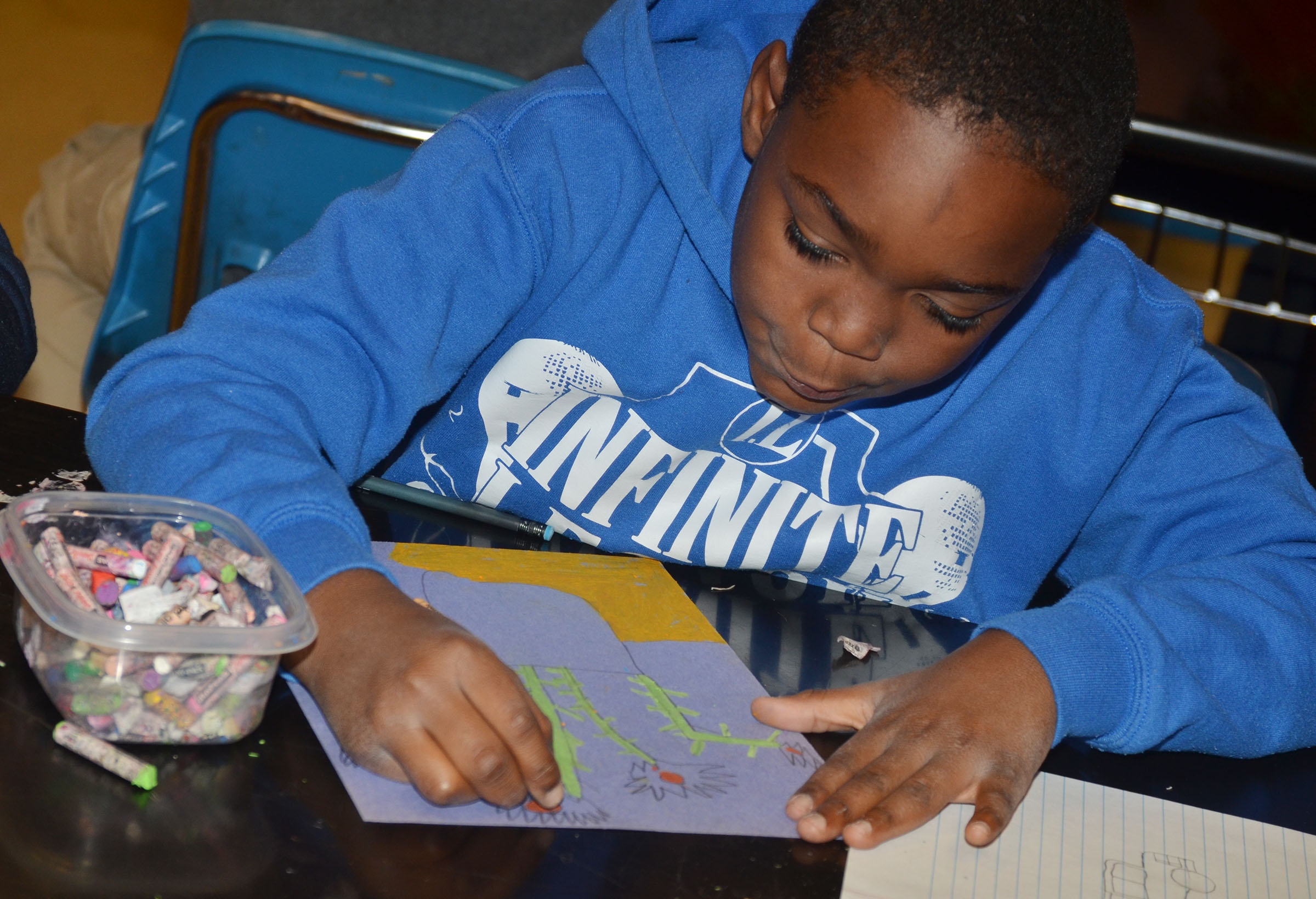CMS fourth-grader Deason Smith colors his sunflower drawing with oil pastels.