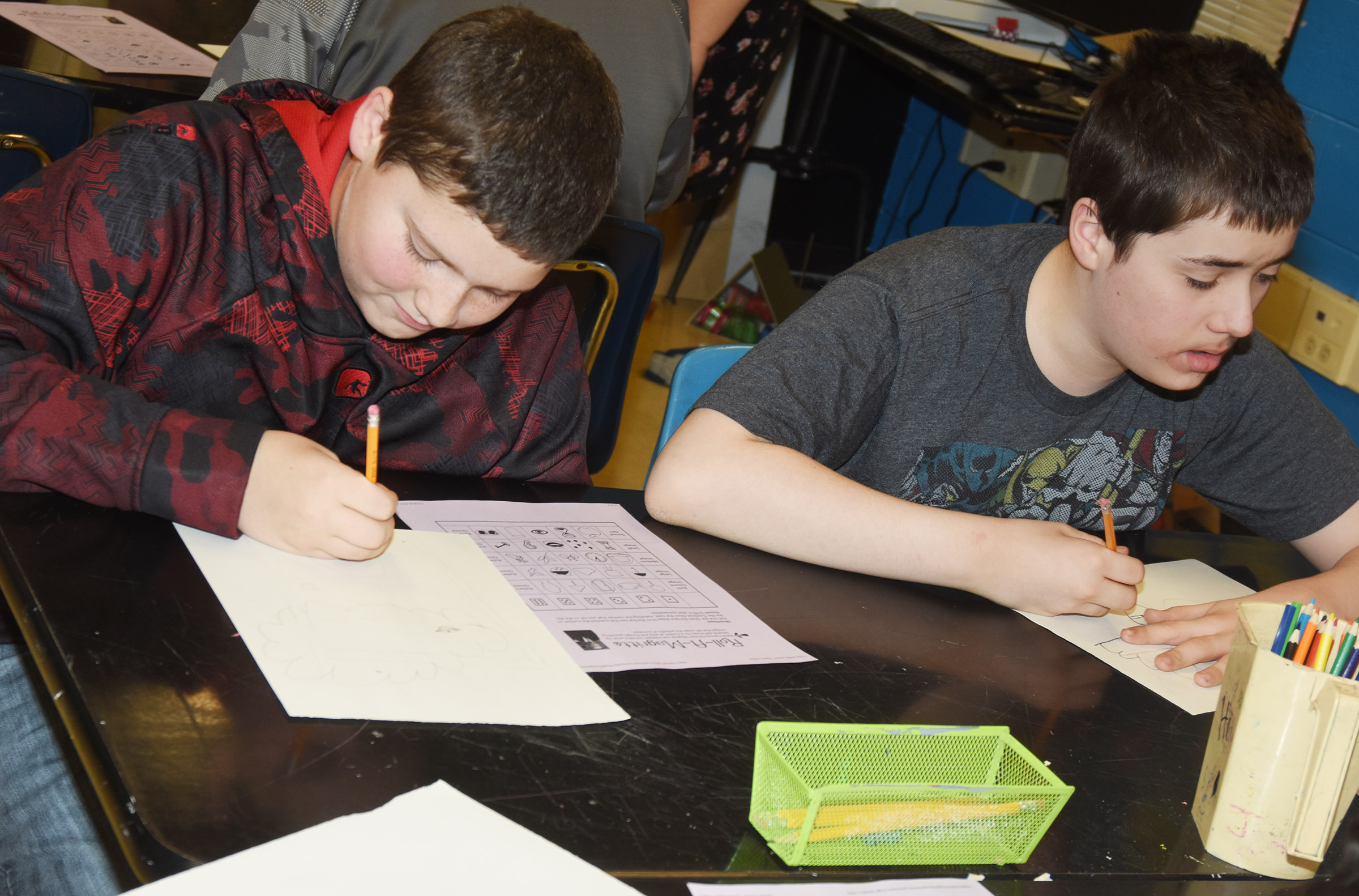 CMS sixth-graders Johnathon Foster, at left, and Taz Shipione draw their surrealism artwork.