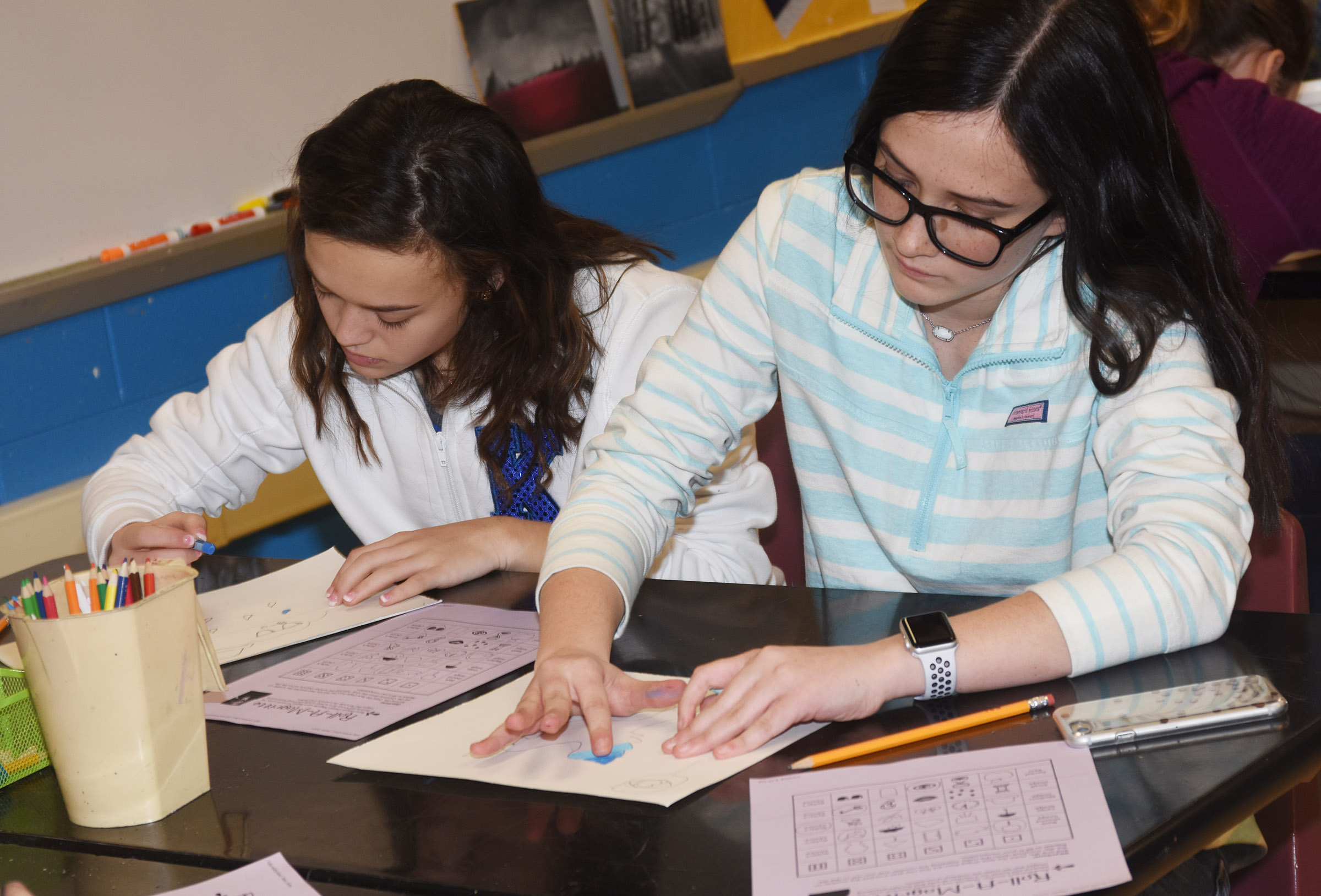 CMS eighth-graders Tayler Thompson, at left, and Sarah Adkins add oil pastels to their surrealism artwork.
