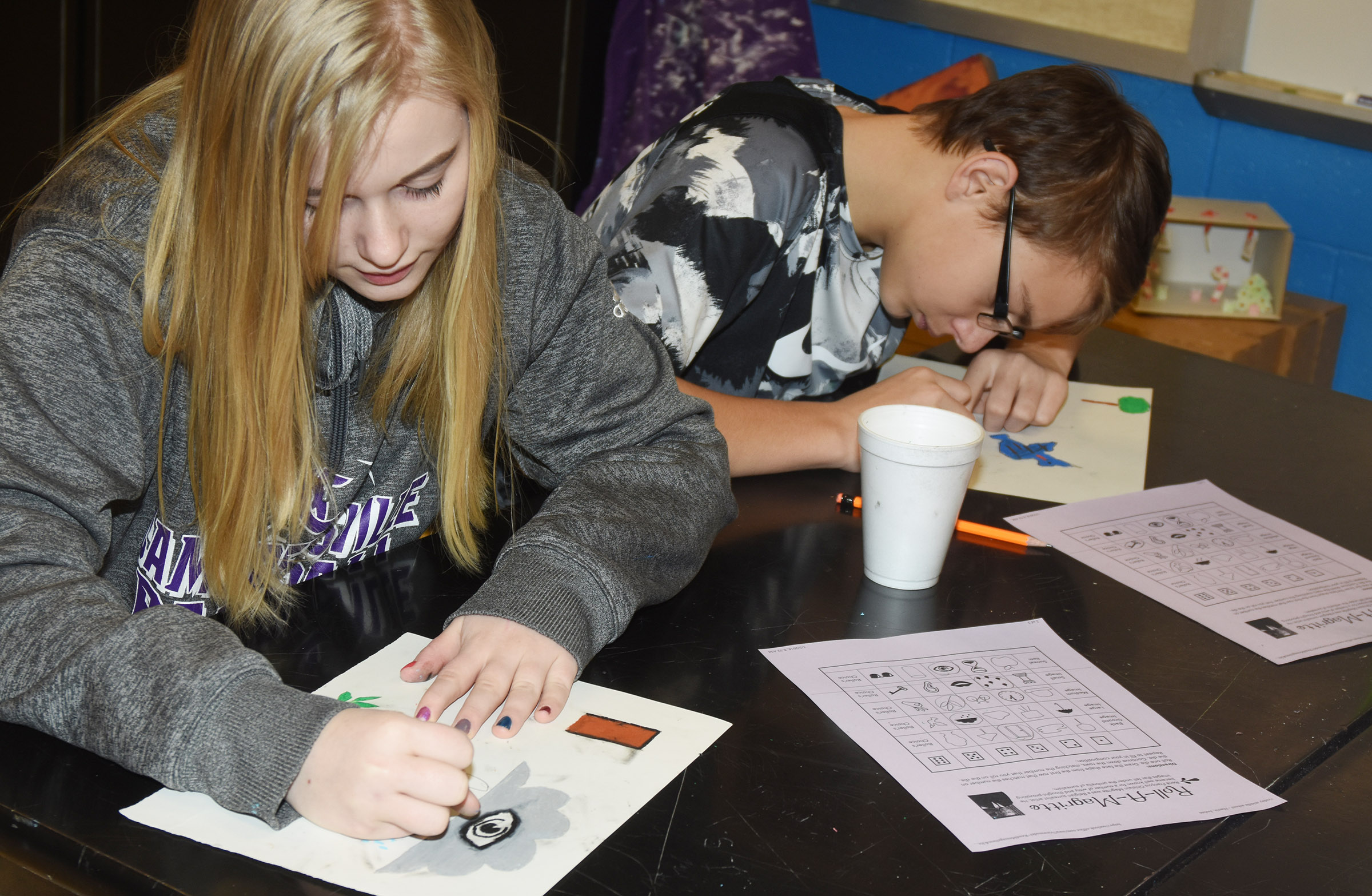 CMS eighth-graders Gabby Skaggs, at left, and Jarred Mays add color to their surrealism artwork.