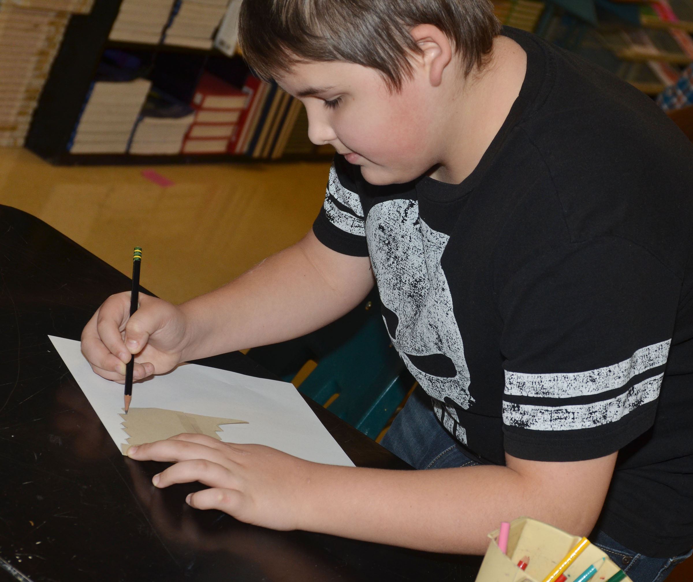 CMS seventh-grader Kaine Terry traces his tessellation.