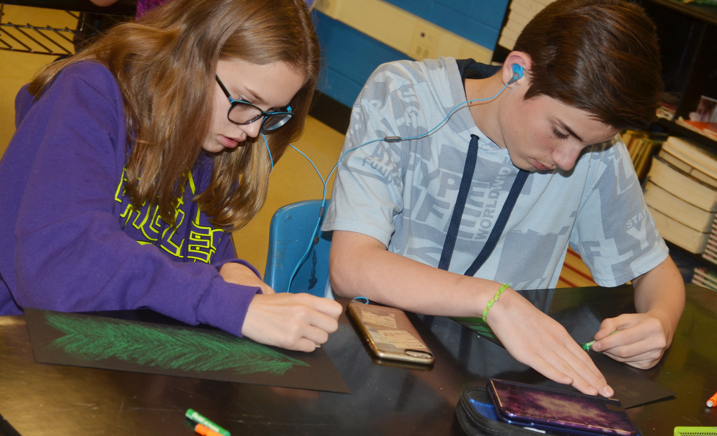CMS sixth-graders Chloe Thompson, at left, and Isaac Garrison create their trees.