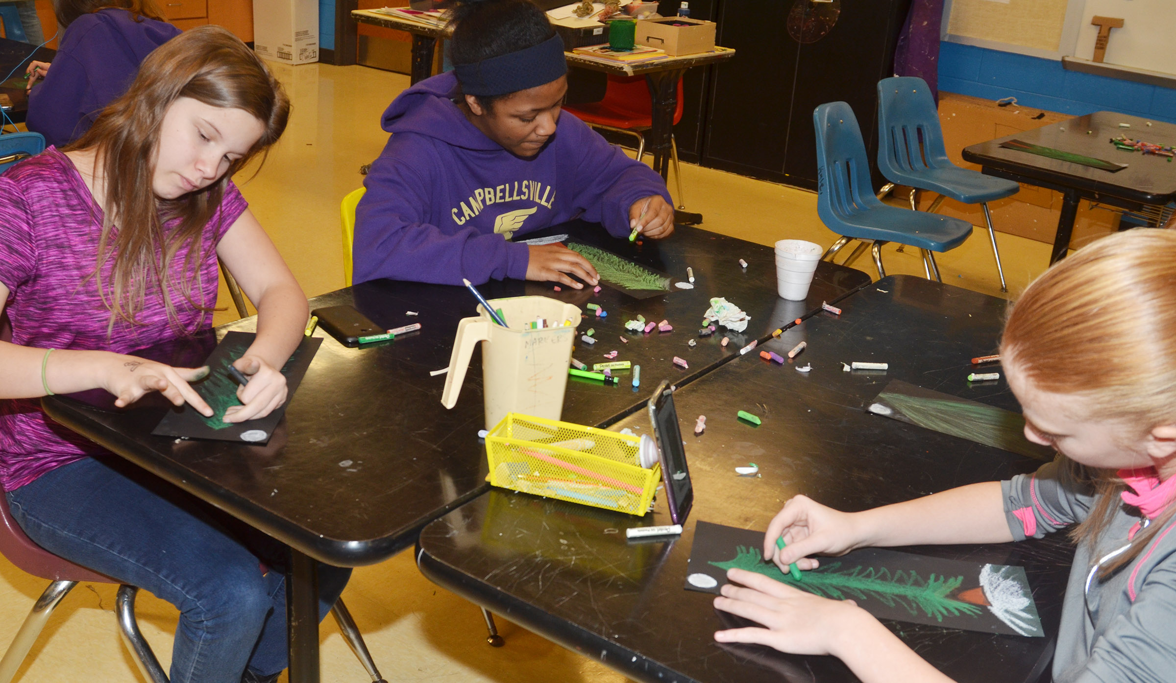 From left, CMS seventh-grader Forever Tungate, sixth-grader Camilla Taylor and eighth-grader Hayley Wethington create their trees.