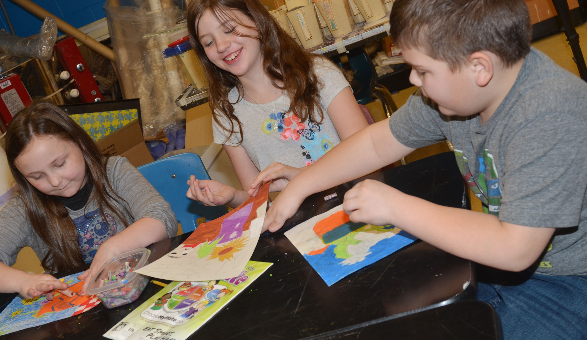 From left, CMS fourth-grader Shyanna Young, sixth-grader Mikaela Scharbrough and fourth-grader Logan England color their sunflower drawings with oil pastels.
