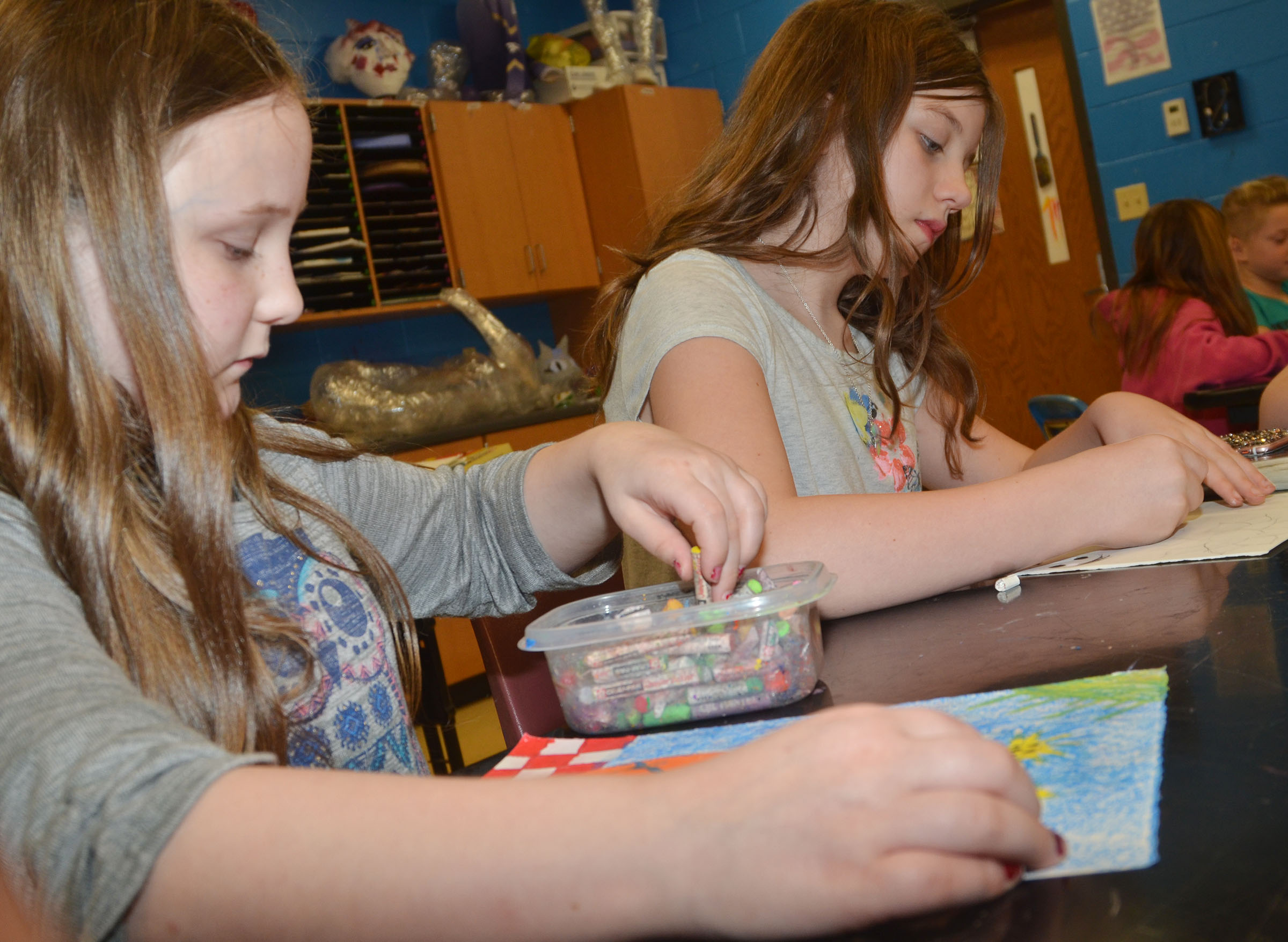 CMS fourth-grader Shyanna Young, at left, and sixth-grader Mikaela Scharbrough color their sunflower drawings.