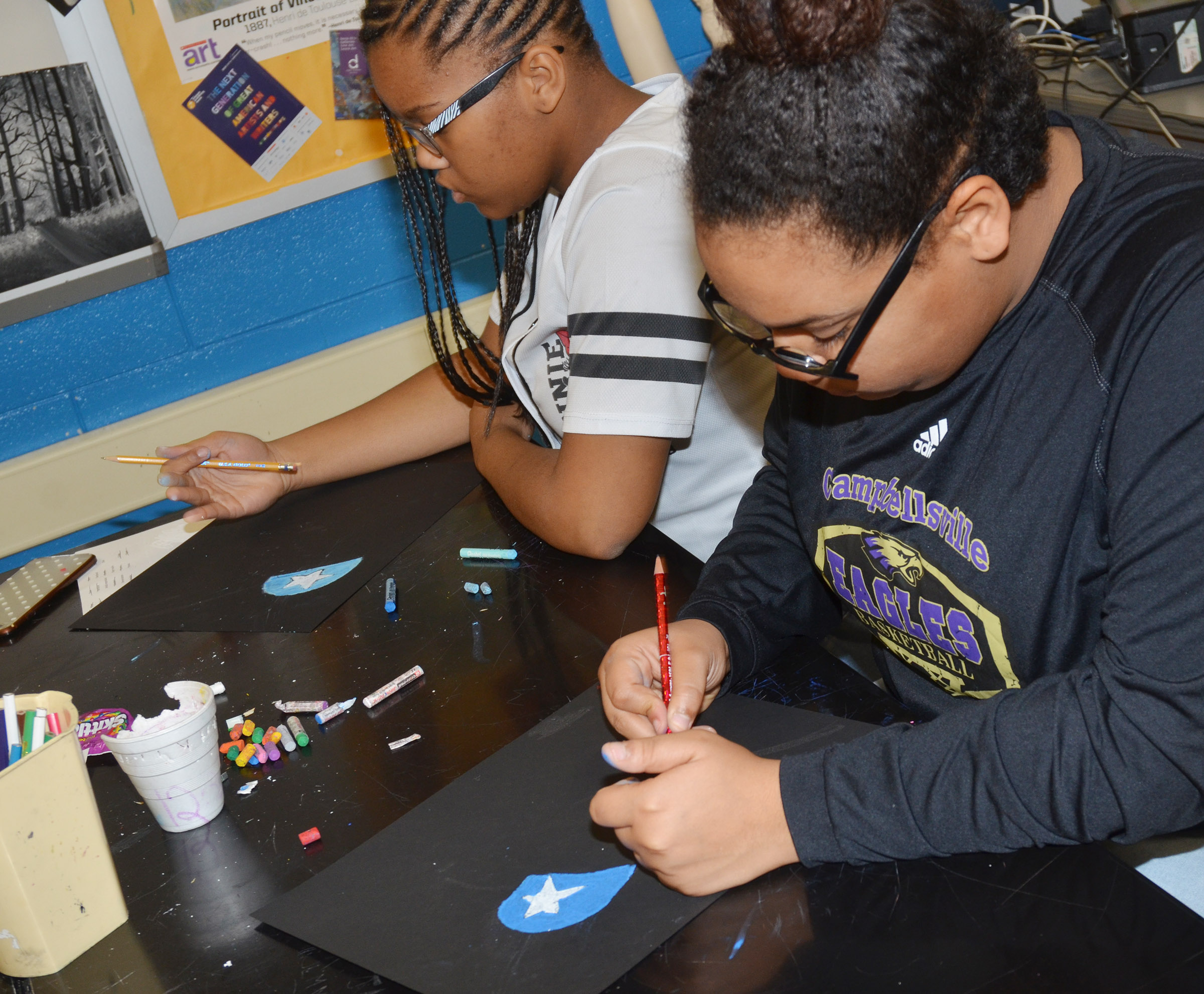 CMS seventh-grader Antaya Epps, at left, and eighth-grader Brae Washington add color to their hearts.