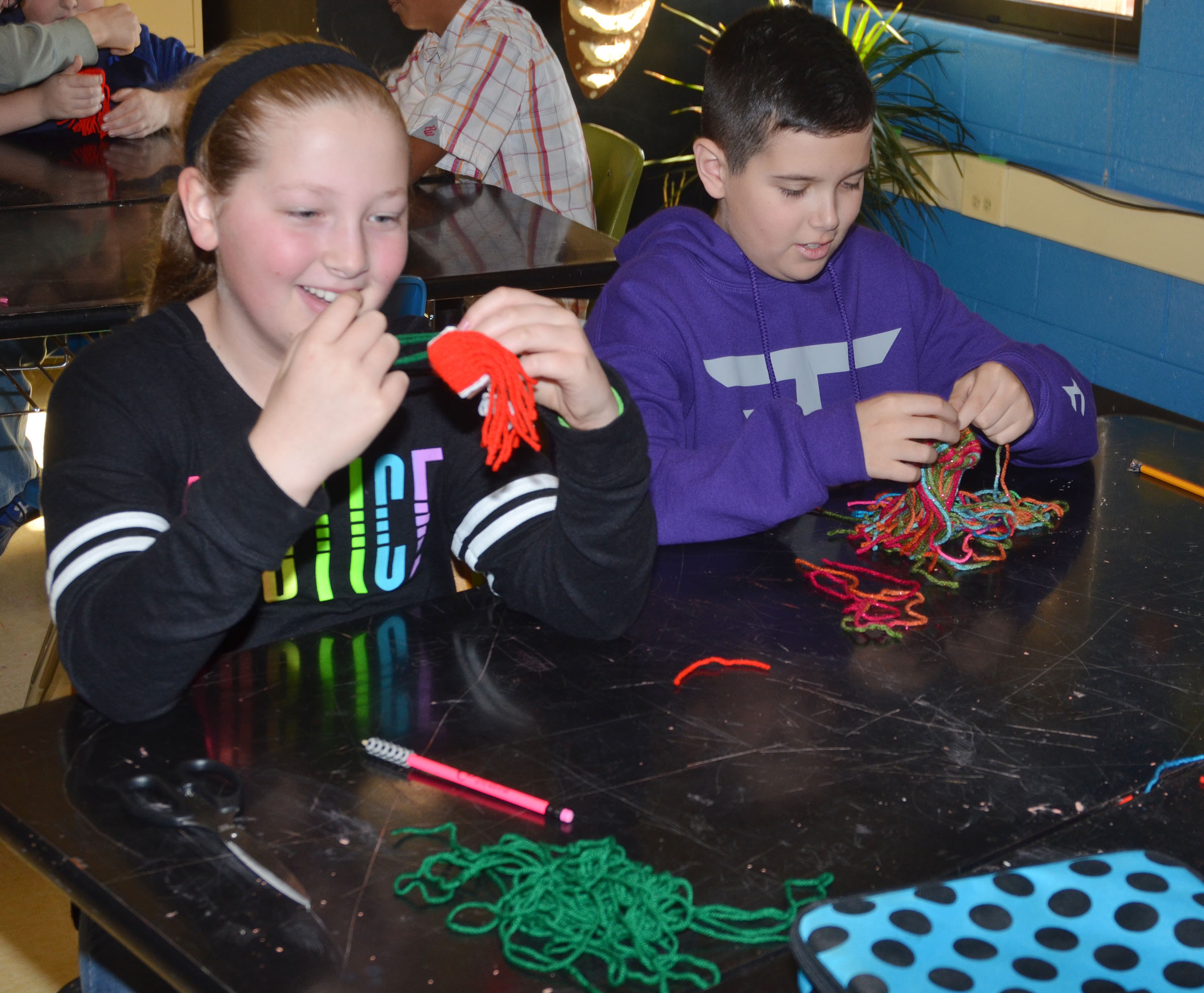 CMS fifth-graders Ava Hughes, at left, and Chase Lawless use yarn to make miniature toboggans.