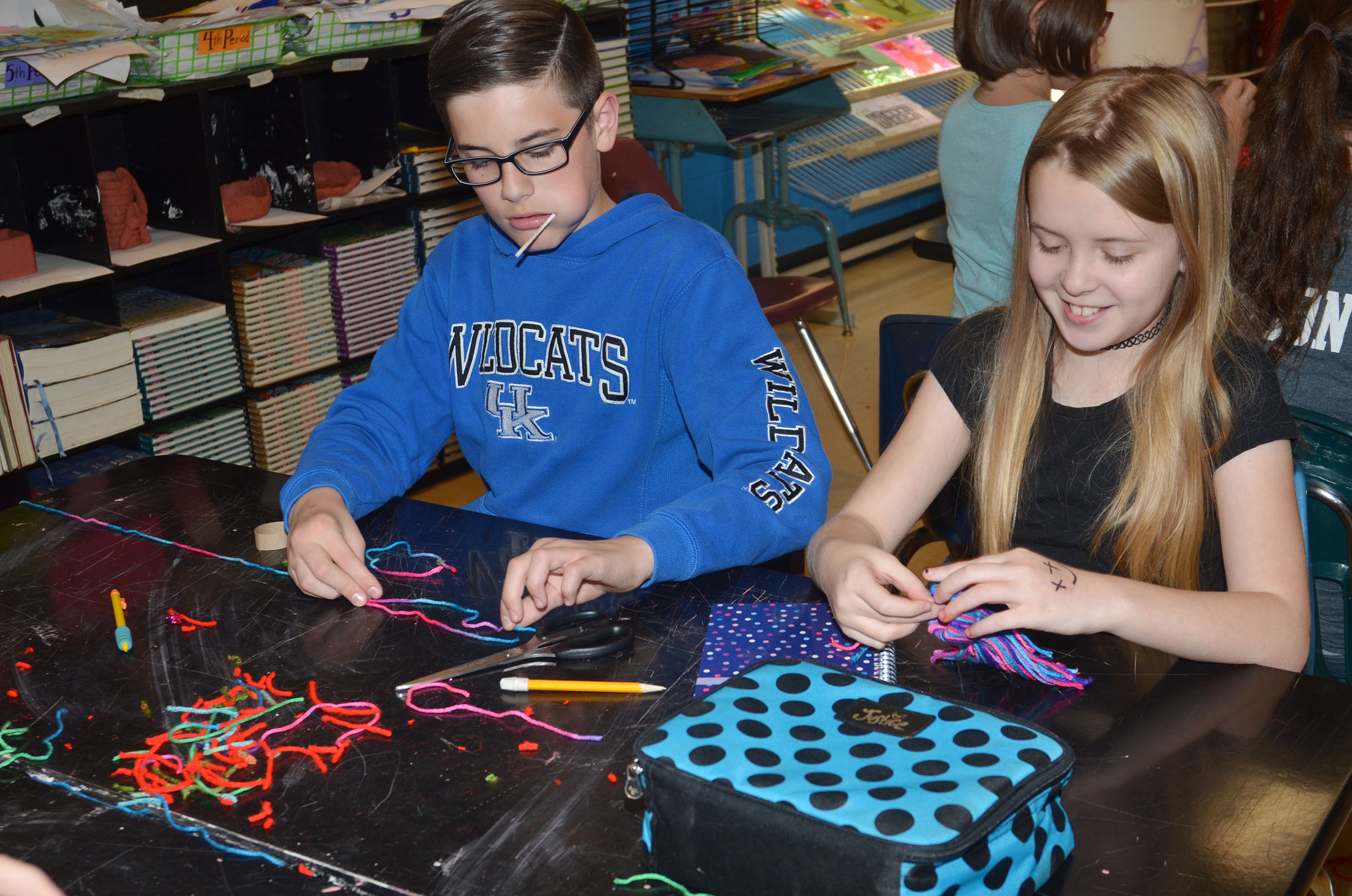 CMS fifth-graders Isaac Garrison, at left, and Jaylie Moore make toboggans out of yarn.