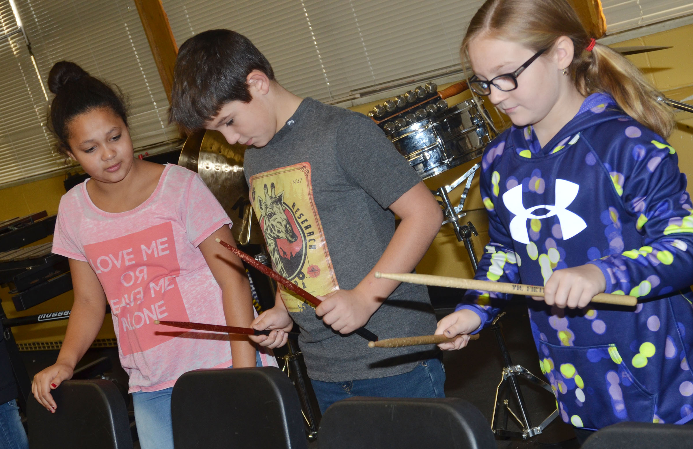 From left, CMS fourth-graders Kenya Bridgewater, Kace Eastridge and Lilyan Murphy practice keeping a steady beat with their drum sticks.