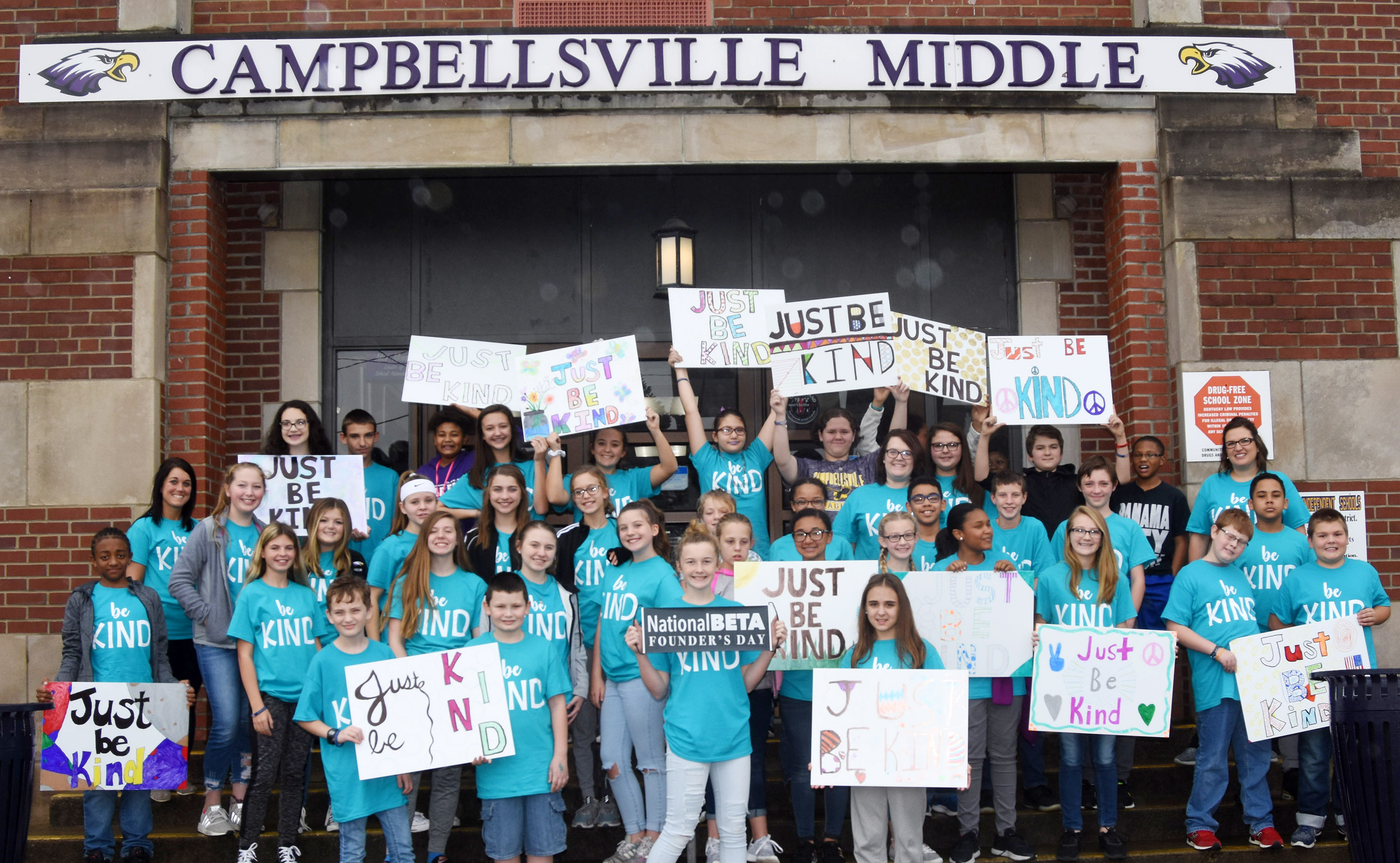 "CMS Beta Club members hold their ""Just Be Kind"" signs before traveling to post them at local businesses."