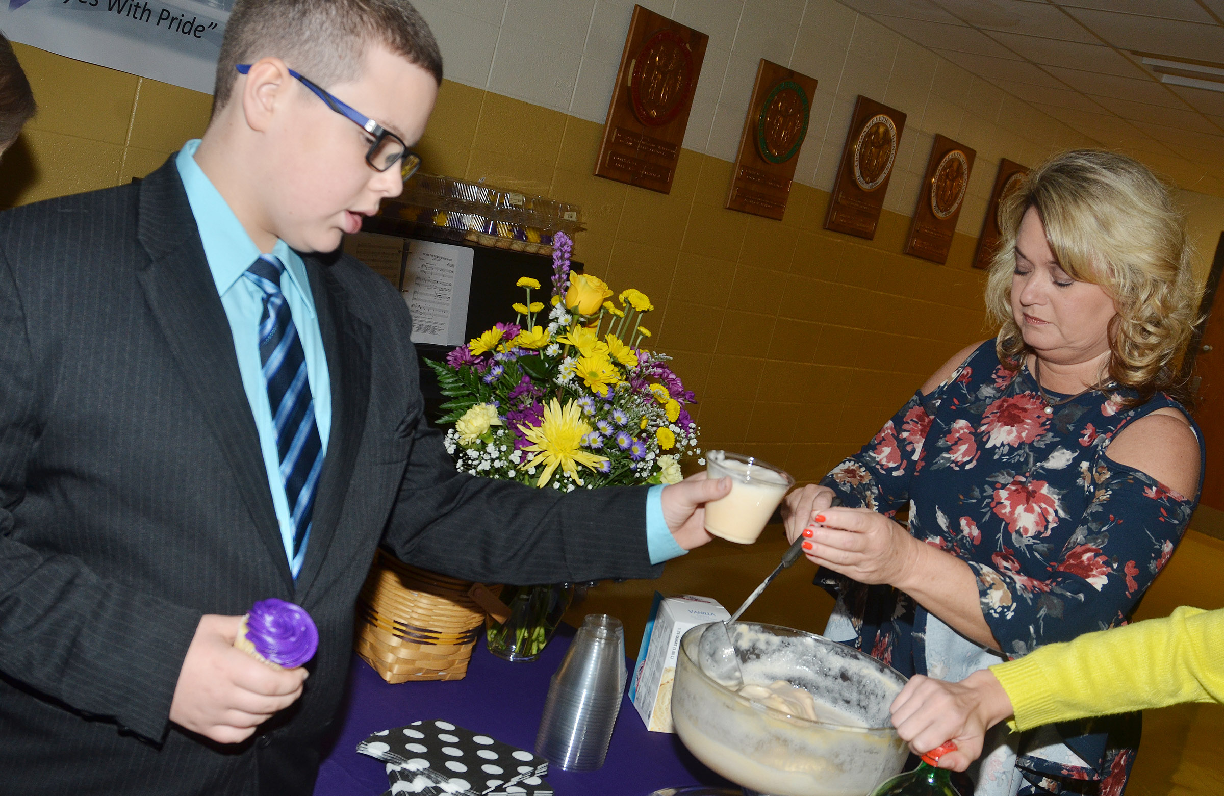 CMS sixth-grader Daniel Caton is served punch at a reception following the ceremony. At right is Campbellsville High School bookkeeper Kim Thompson.