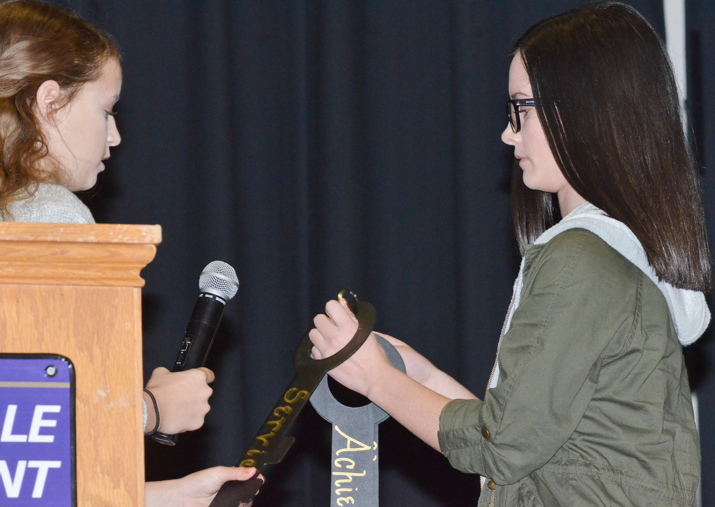 CMS Beta member and eighth-grader Rylee Petett, at left, places the key of service on the keyring as vice president and eighth-grader Sarah Adkins holds it.