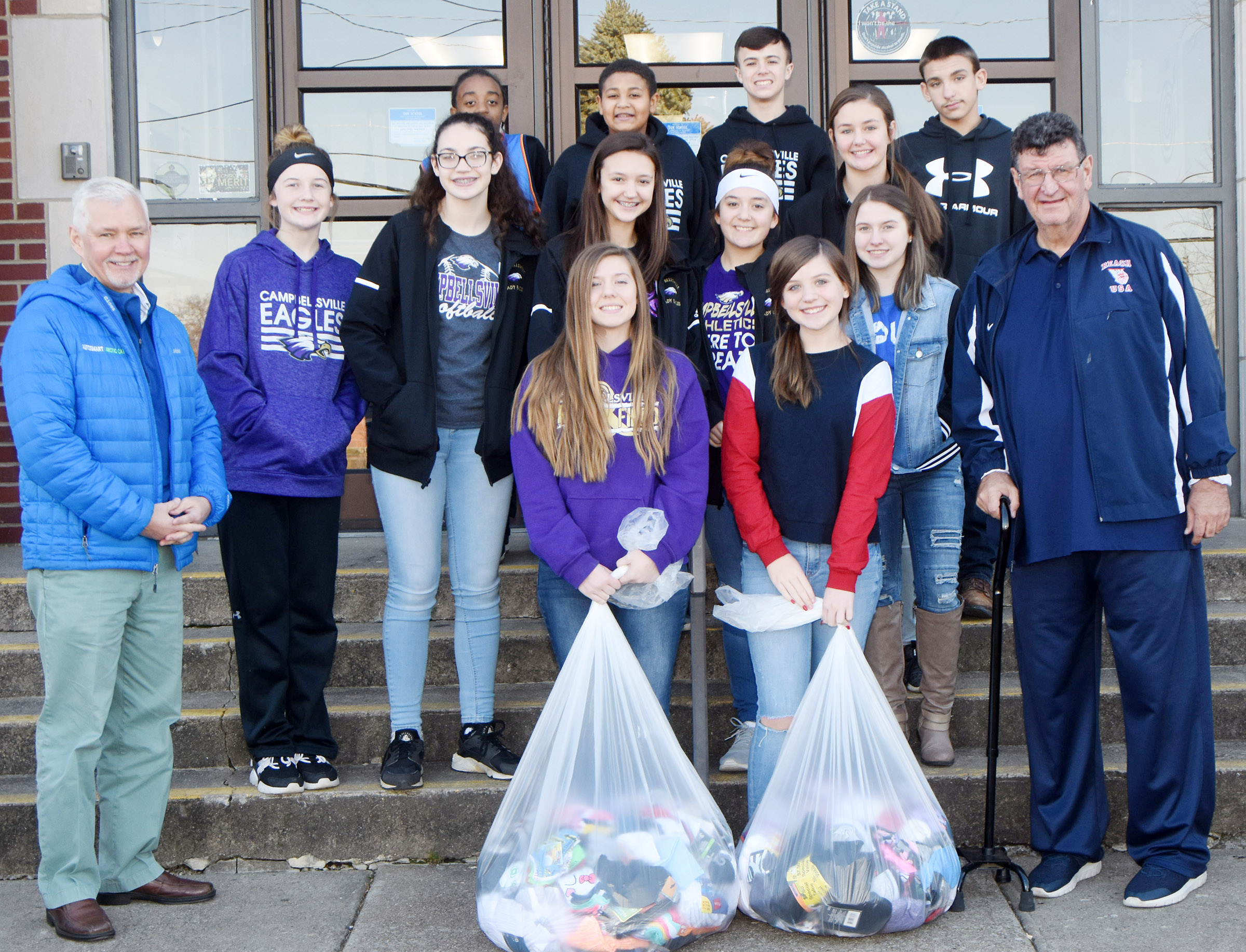 CMS Junior Beta Club members present the socks they recently collected to Stan Curry, at left, and Robby Speer, at right, of the Sports Reach organization. The socks were donated to Owsley County residents. Pictured with Curry and Speer are, from left, front, eighth-graders Alysa Howard and Mikaela Scharbrough. Second row, eighth-graders Dakota Slone, Mary Russell, Bri Hayes, Bri Davis and Leigh Hicks. Back, eighth-graders Zamar Owens, Ronin Smith, Chase Hord, Haylee Allen and Nate Mitchell.