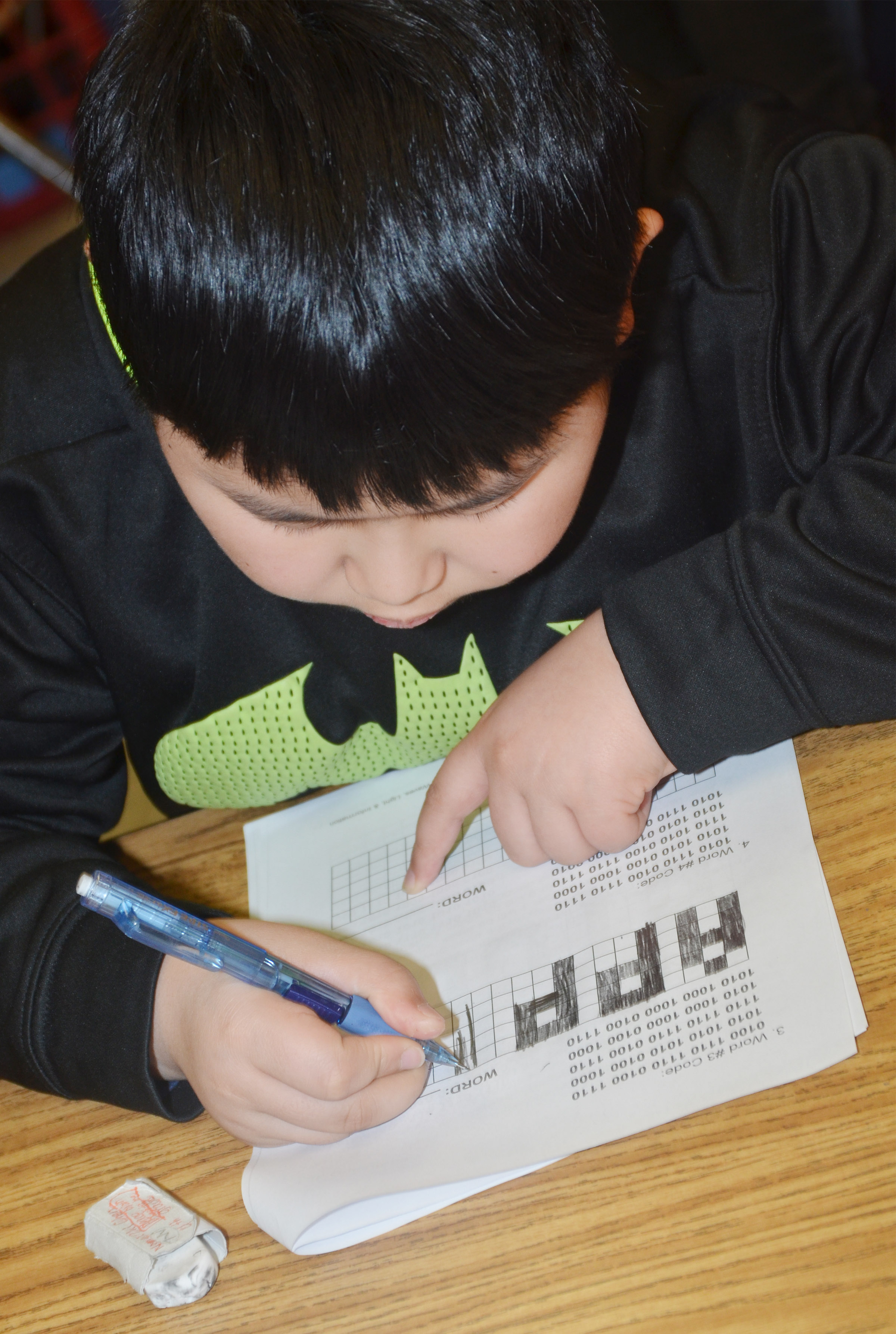 "CMS fourth-grader Zhi Chen deciphers a binary code to reveal the word ""apples."""