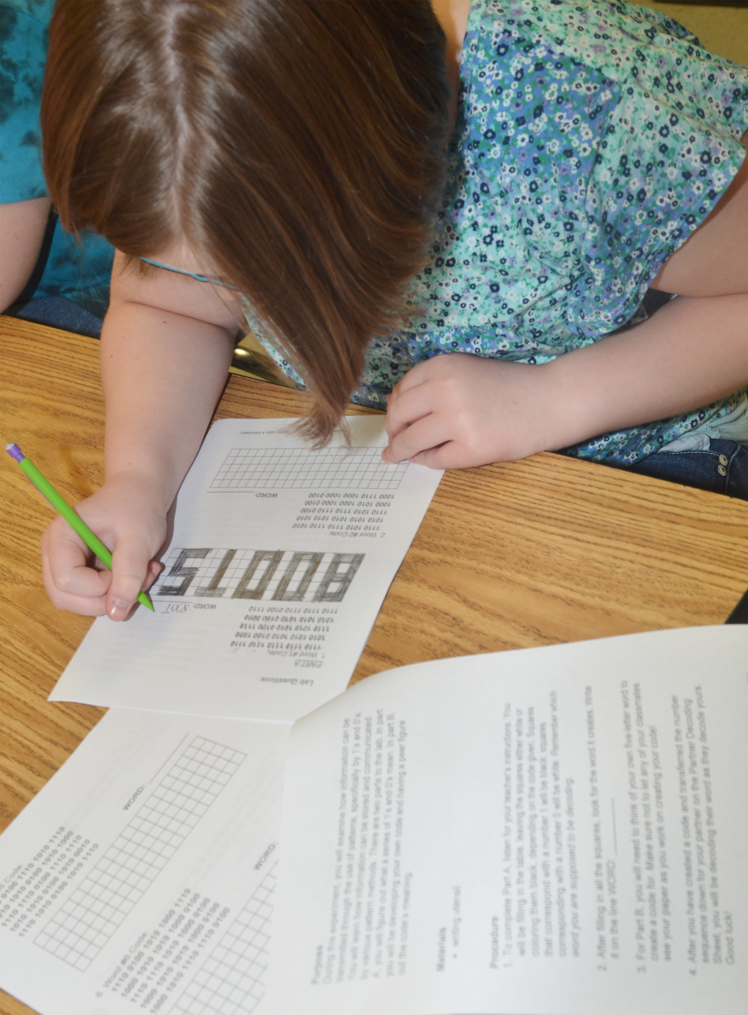 "CMS fourth-grader Keeley Dicken deciphers a binary code to reveal the word ""boots."""