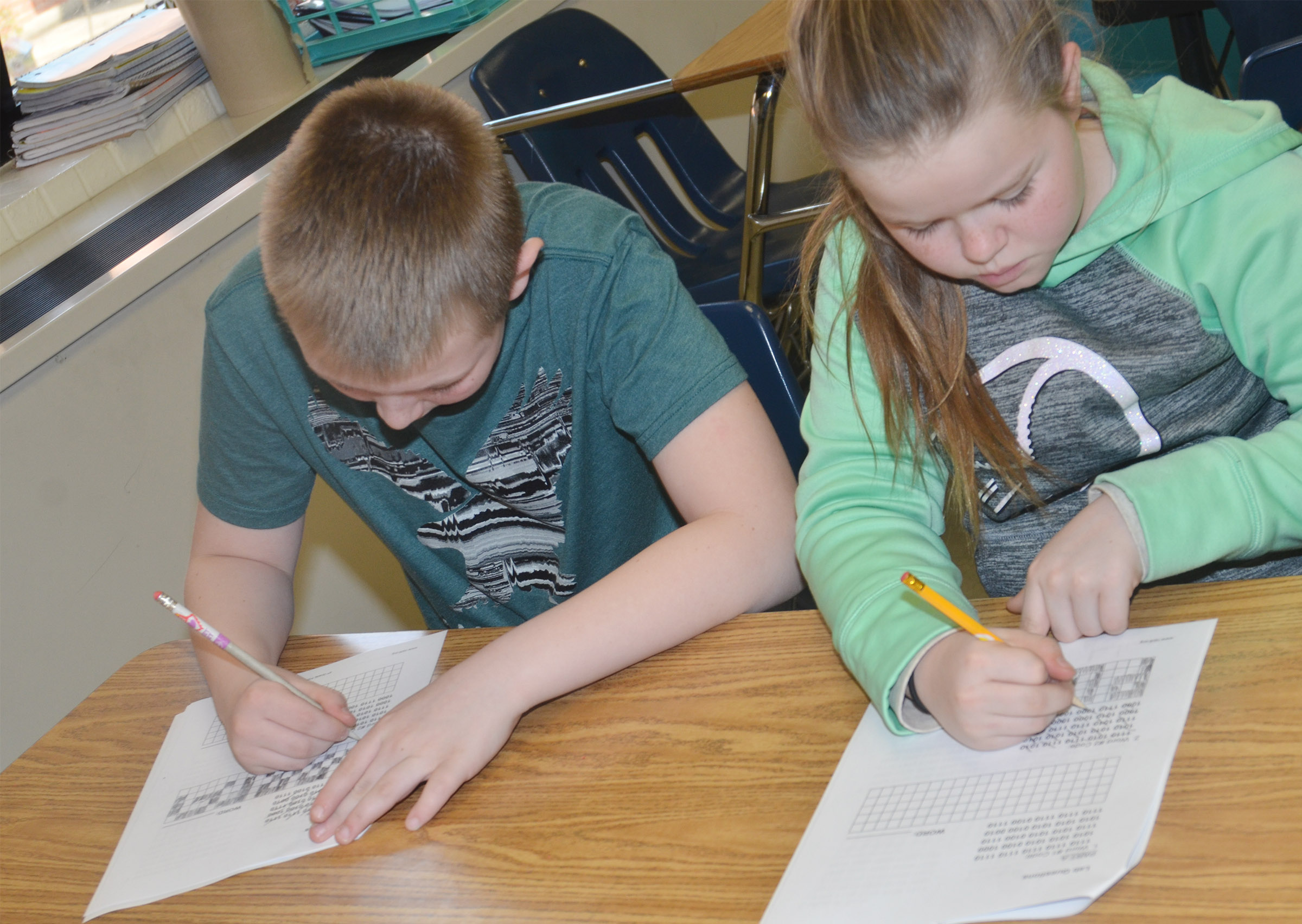 CMS fourth-graders Kaleb Miller, at left, and Miley Hash decipher binary codes.